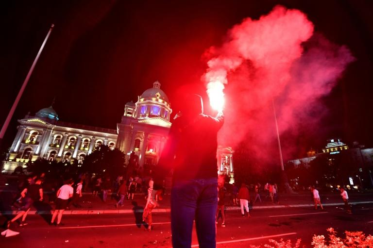 A protestor holds a flare as Serbian police fires tear gas in front of the National Assembly building in Belgrade, on July 7, 2020, to disperse thousands of protesters angry at the return of a weekend coronavirus curfew. (AFP Photo/Andrej ISAKOVIC)