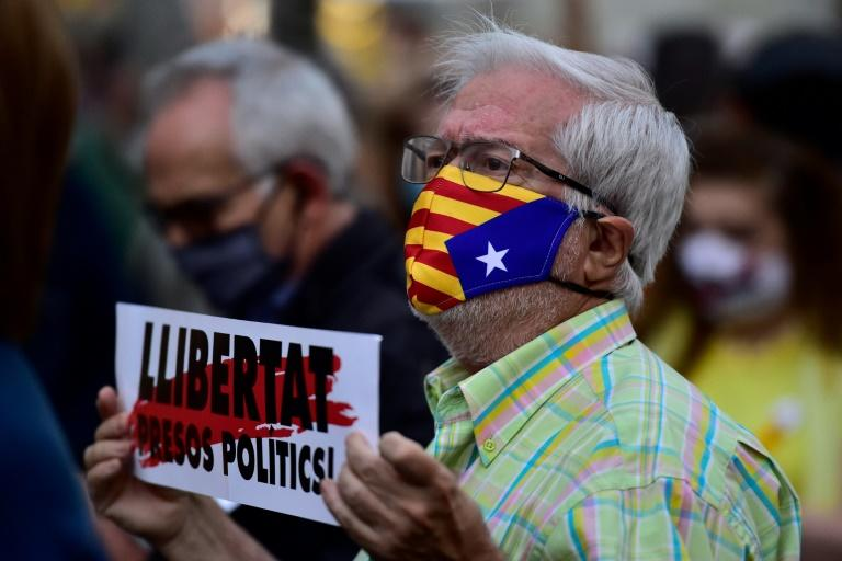 "A man wearing a face mask bearing the Catalan pro-independence flag holds a placard reading ""Free political prisoners"""