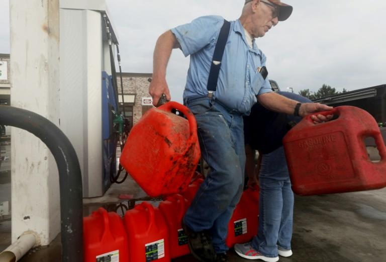 A man returns unfilled cans back to a truck after finding there was no gasoline left at a station in Lacassine, Louisiana as people prepare for Hurricane Delta on October 8, 2020