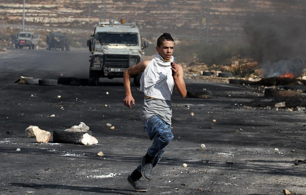 A Palestinian stone thrower takes cover from Israeli security forces during clashes in Beit El, near the West Bank city of Ramallah, on October 8, 2015 (AFP Photo/Abbas Momani)