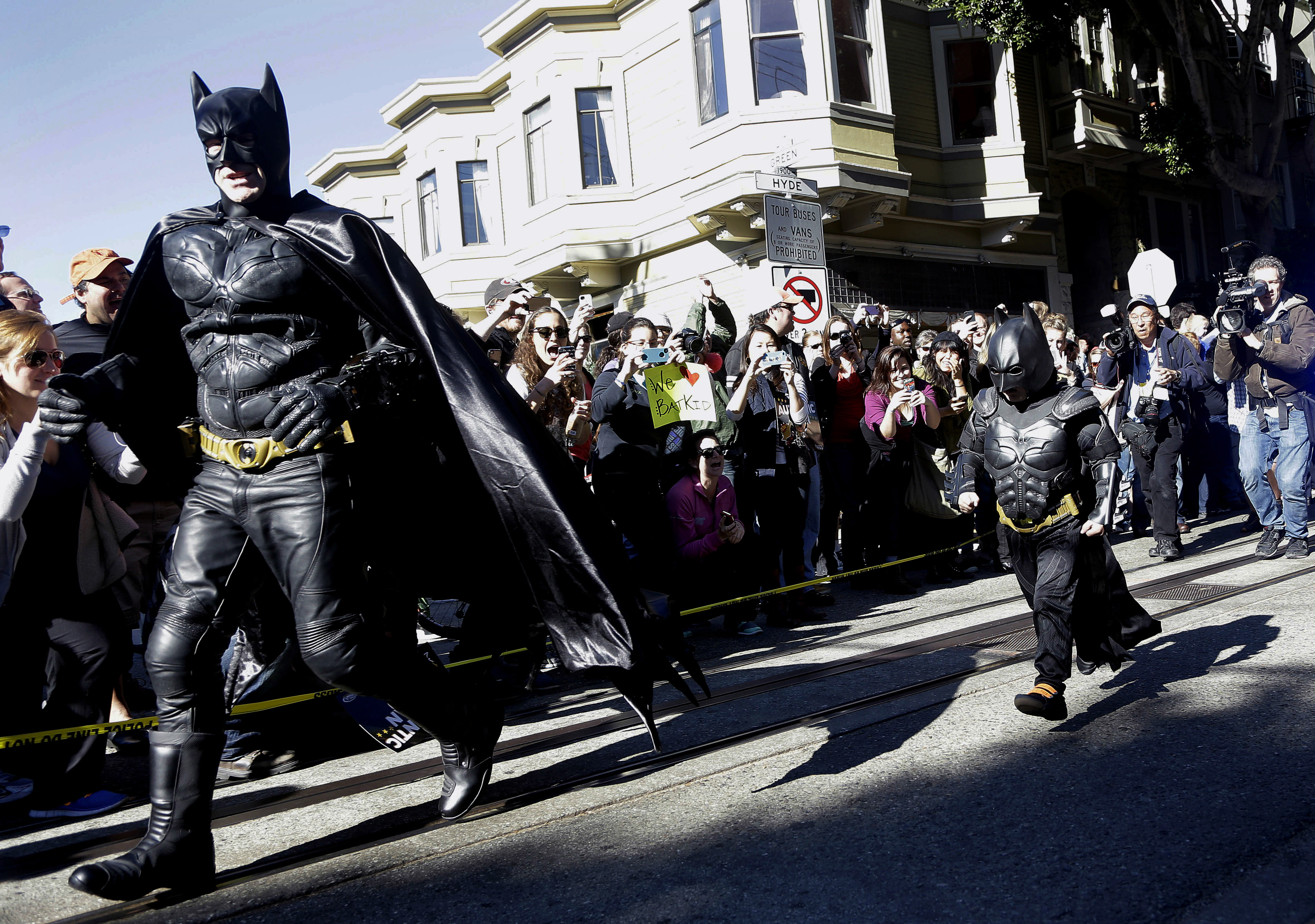 "Miles Scott, dressed as Batkid, right, runs with Batman after saving a damsel in distress in San Francisco, Friday, Nov. 15, 2013. San Francisco turned into Gotham City on Friday, as city officials helped fulfill Scott's wish to be ""Batkid."" Scott, a leukemia patient from Tulelake in far Northern California, was called into service on Friday morning by San Francisco Police Chief Greg Suhr to help fight crime, The Greater Bay Area Make-A-Wish Foundation says. (AP Photo/Jeff Chiu)"