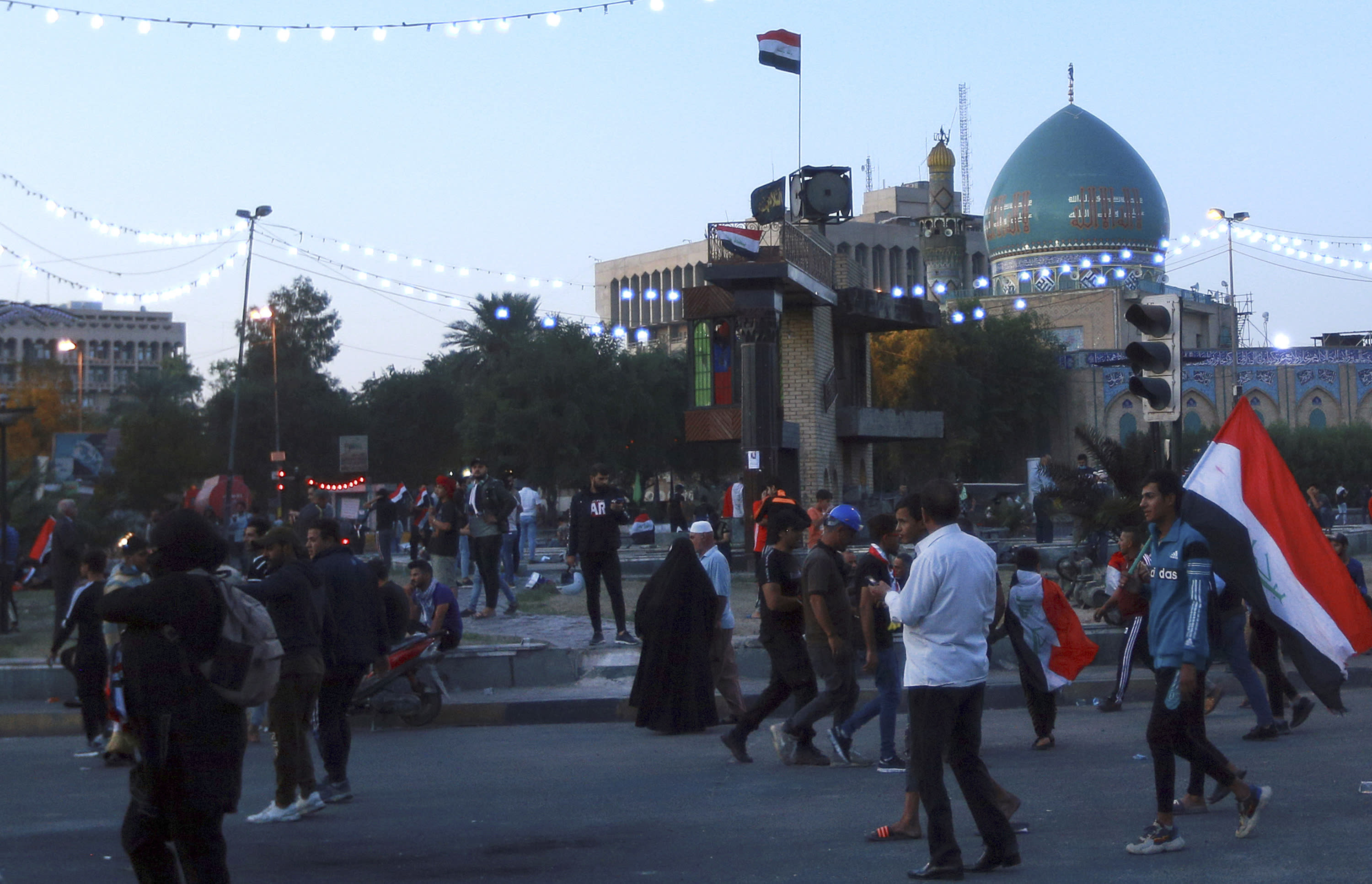 People walk at the Khilani Square after protesters took its control and reopened it after the clashes between Iraqi security forces and anti-government demonstrators in Baghdad, Iraq, Saturday, Nov. 16, 2019. (AP Photo/Hadi Mizban)