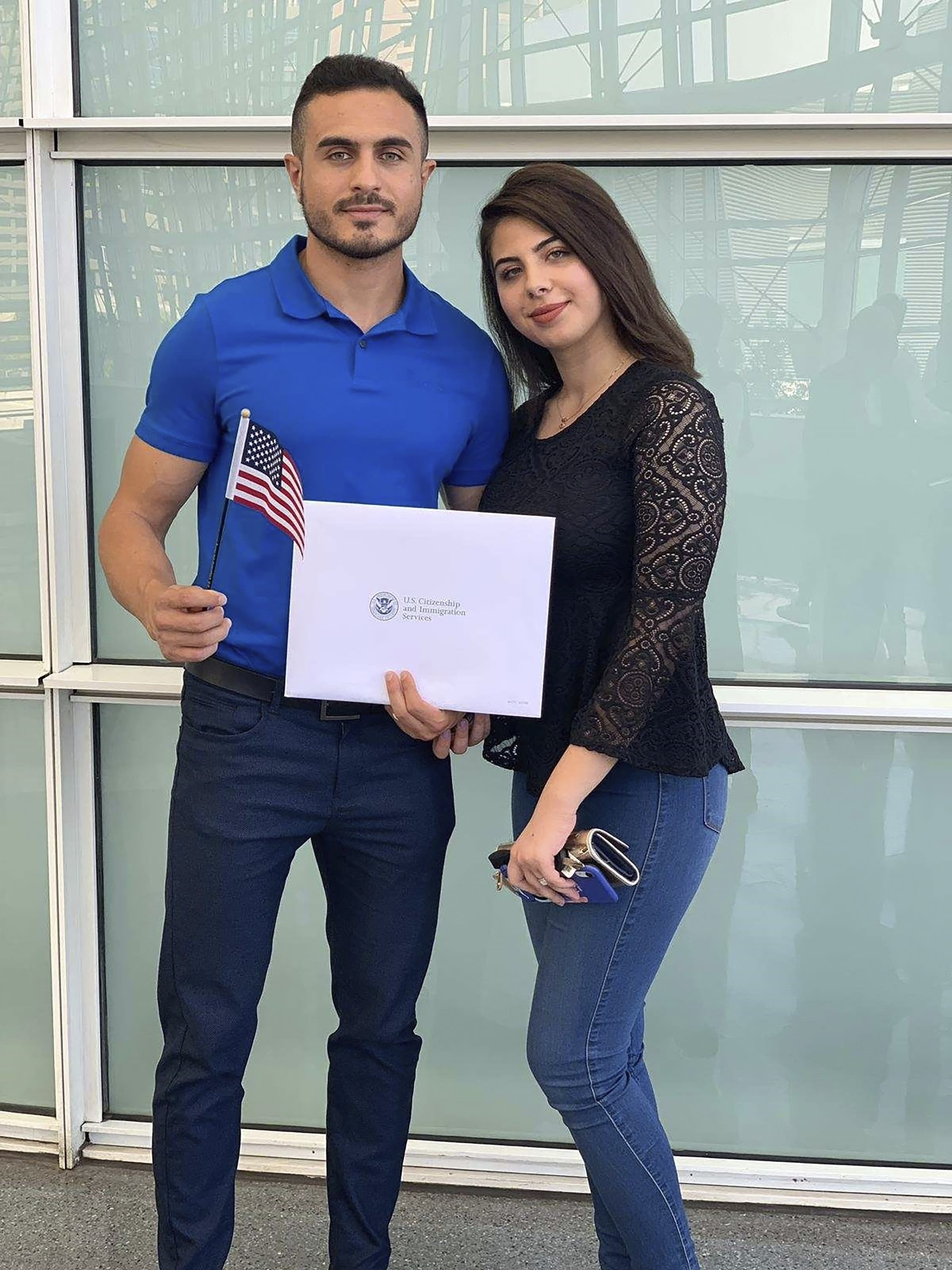 """In this September 2019, photo provided by Jad """"Jay"""" Jawad, Jawad, left, who came to the U.S. as a refugee from war-torn Iraq, poses at his naturalization ceremony in Phoenix with his wife, Nagham Rabeea, right. Jawad's parents and siblings are also settled in Arizona. He said that during presidential elections in his native country, Saddam Hussein was the only candidate on the ballot and the only real option was """"yes,"""" because a """"no"""" vote could get you jailed or worse. Now, he said he is looking to voting freely in his first U.S. presidential election this fall. (Jad """"Jay"""" Jawad via AP)"""