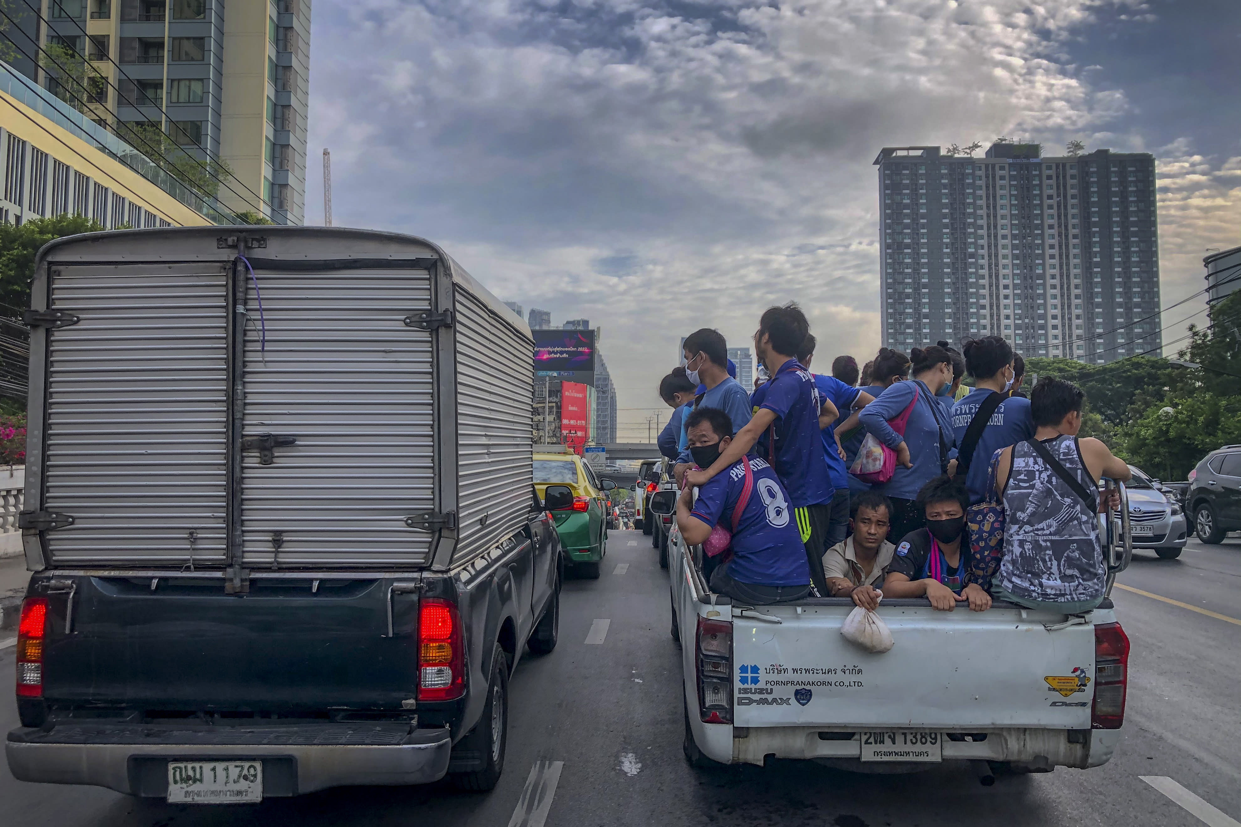 Migrant construction workers, some wearing face masks, travel in the back of a crew cab in Bangkok, Thailand, Monday, May 25, 2020. Thai government continue to ease restrictions related to running business in capital Bangkok that were imposed weeks ago to combat the spread of COVID-19. (AP Photo/Gemunu Amarasinghe)