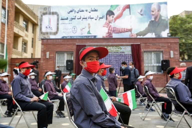 Mask-clad schoolchildren sit in Tehran in September 2020 before a billboard featuring the image of late general Qasem Soleimani