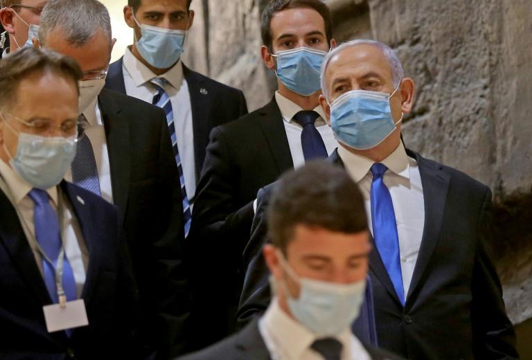 Netanyahu (R), wearing a protective face mask, arrives for the swearing-in ceremony of an unprecedented power-sharing government formed with one-time rival Benny Gantz at the Israeli parliament (AFP Photo/)