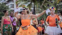Vestidos de laranja, foliões fazem bloco em frente ao condomínio de Bolsonaro, no Rio