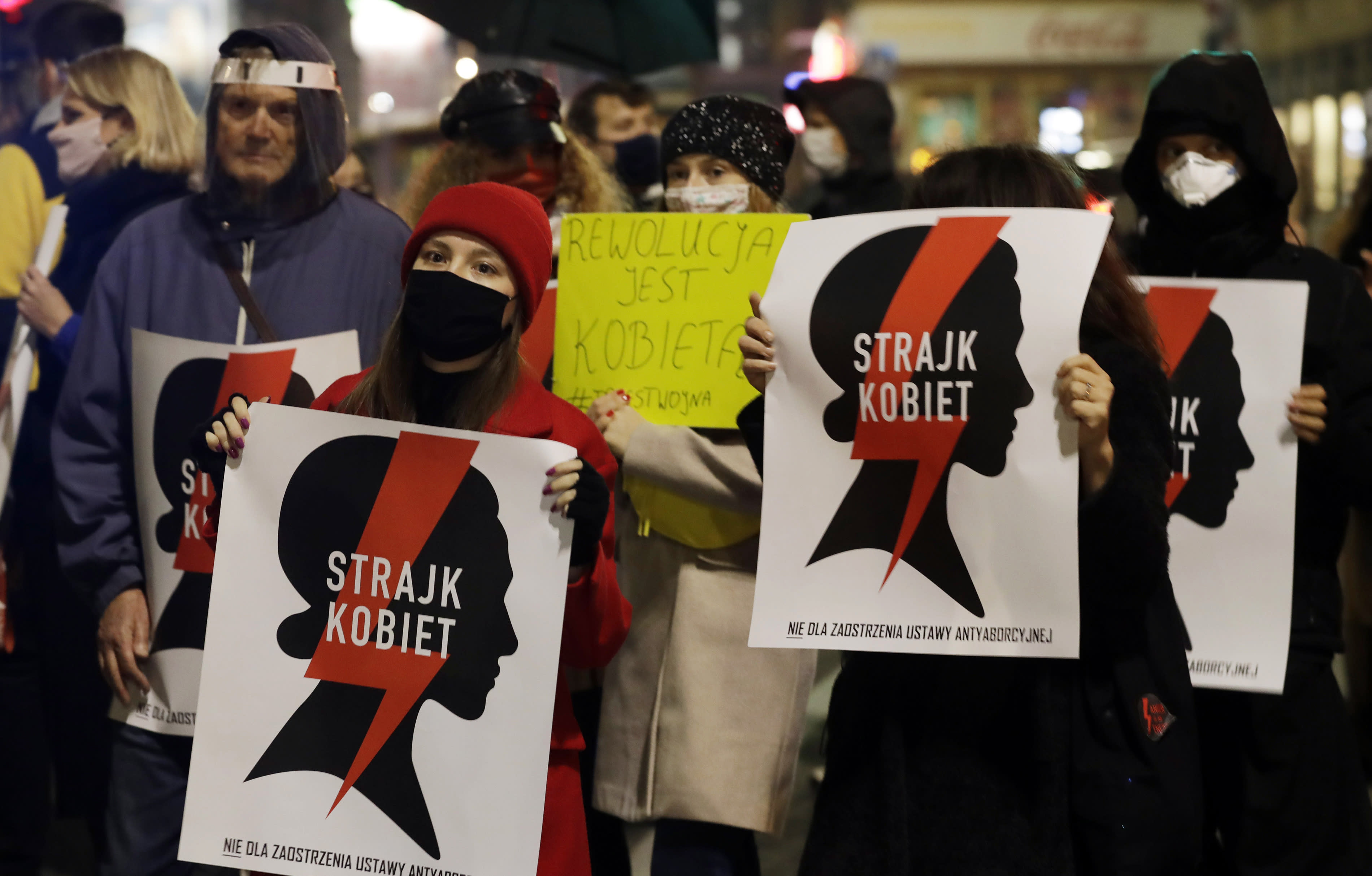 """Protesters hold signs reading in Polish """"women's strike"""" as they block a crossing in downtown Warsaw, Monday, Nov. 9, 2020, on the 12th straight day of anti-government protests that were triggered by the tightening of Poland's strict abortion law and are continuing despite a anti-COVID-19 ban on public gatherings. (AP Photo/Czarek Sokolowski)"""
