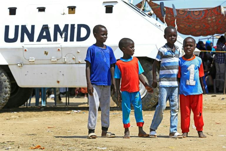 Displaced Sudanese boys pose for a picture in front of a UN-African Union mission to Darfur (UNAMID) vehicle at the Kalma camp for internally displaced people in Darfur's state capital Niyala on October 9, 2019