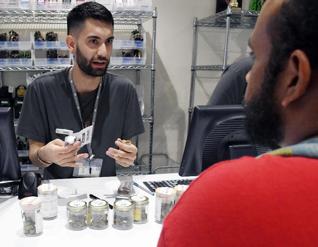 A clerk at a marijuana dispensary serves a customer Saturday, the first day that recreational marijuana became legal in the state of Nevada (AFP Photo/Ethan Miller)