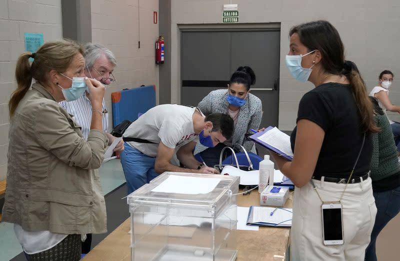 Workers organize papers at a polling station before the start of the voting during the Basque regional elections, amid the coronavirus disease (COVID-19) outbreak, in Durango