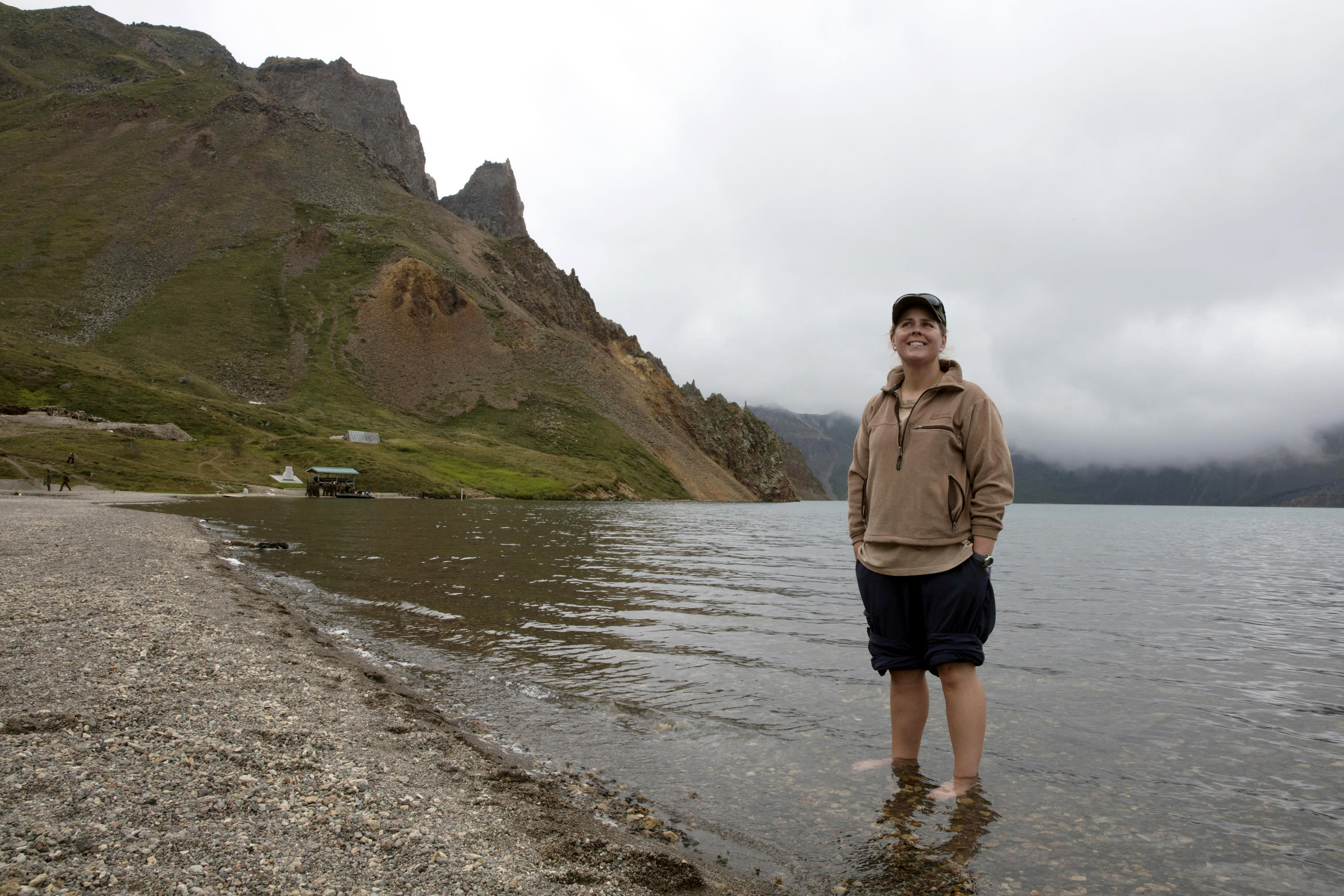 In this Saturday, Aug. 18, 2018, photo, Sinead of Australia stands in the cool water of Lake Chon during a hike arranged by Roger Shepherd of Hike Korea on Mount Paektu in North Korea. Hoping to open up a side of North Korea rarely seen by outsiders, Shepherd, a New Zealander who has extensive experience climbing the mountains of North and South Korea is leading the first group of foreign tourists allowed to trek off road and camp out under the stars on Mount Paektu, a huge volcano that straddles the border that separates China and North Korea. (AP Photo/Ng Han Guan)
