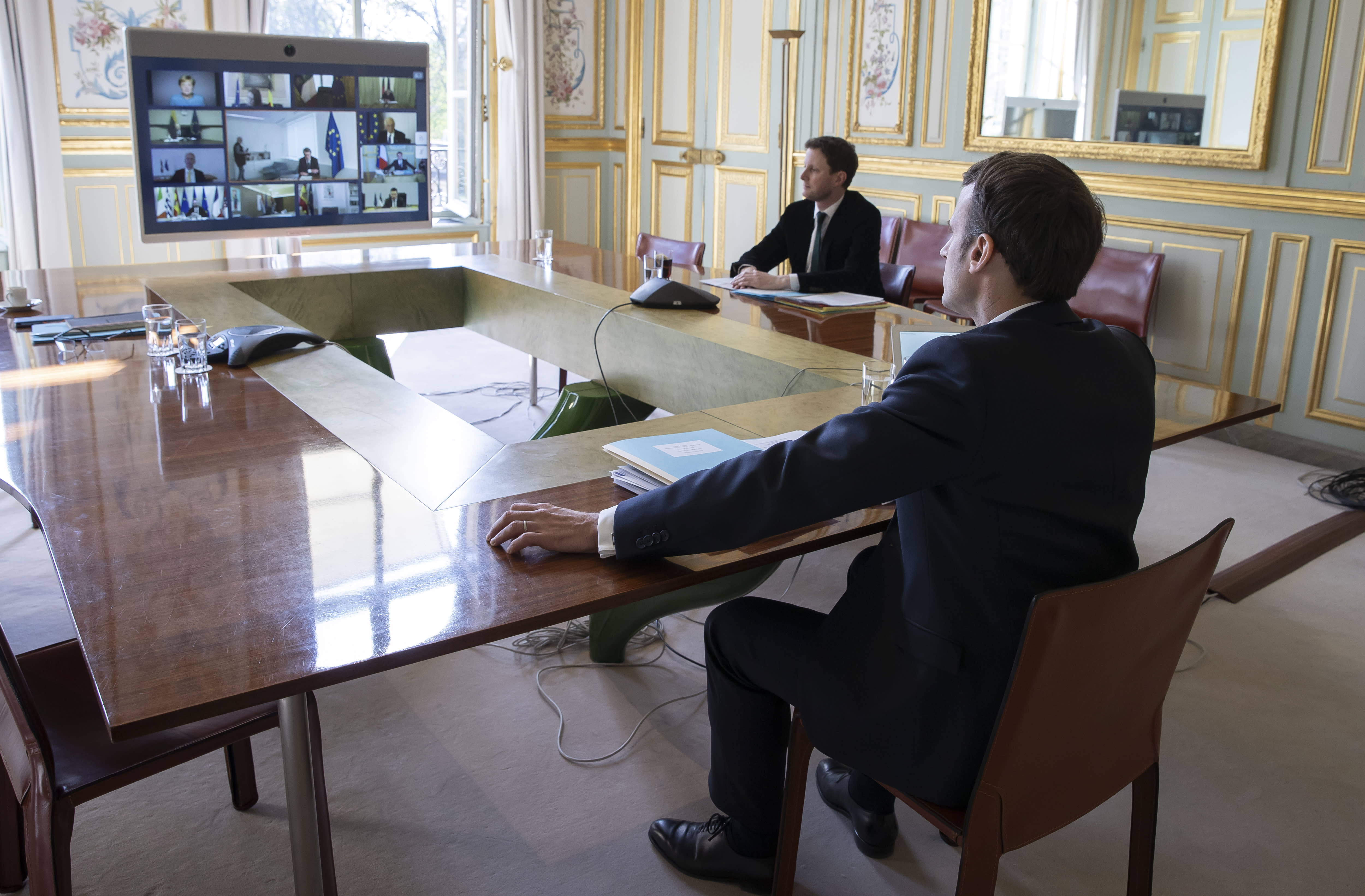 FILE - In this Thursday, March 26, 2020 file photo, French President Emmanuel Macron, right, attends a video conference call with members of the European Council at the Elysee Palace in Paris. European Union leaders are preparing for a new virtual summit, which will take place Thursday, April 23, 2020, to take stock of the damage the coronavirus has inflicted on the lives and livelihoods of the bloc's citizens and to thrash out a more robust plan to revive their ravaged economies. (Ian Langsdon, Pool via AP, File)