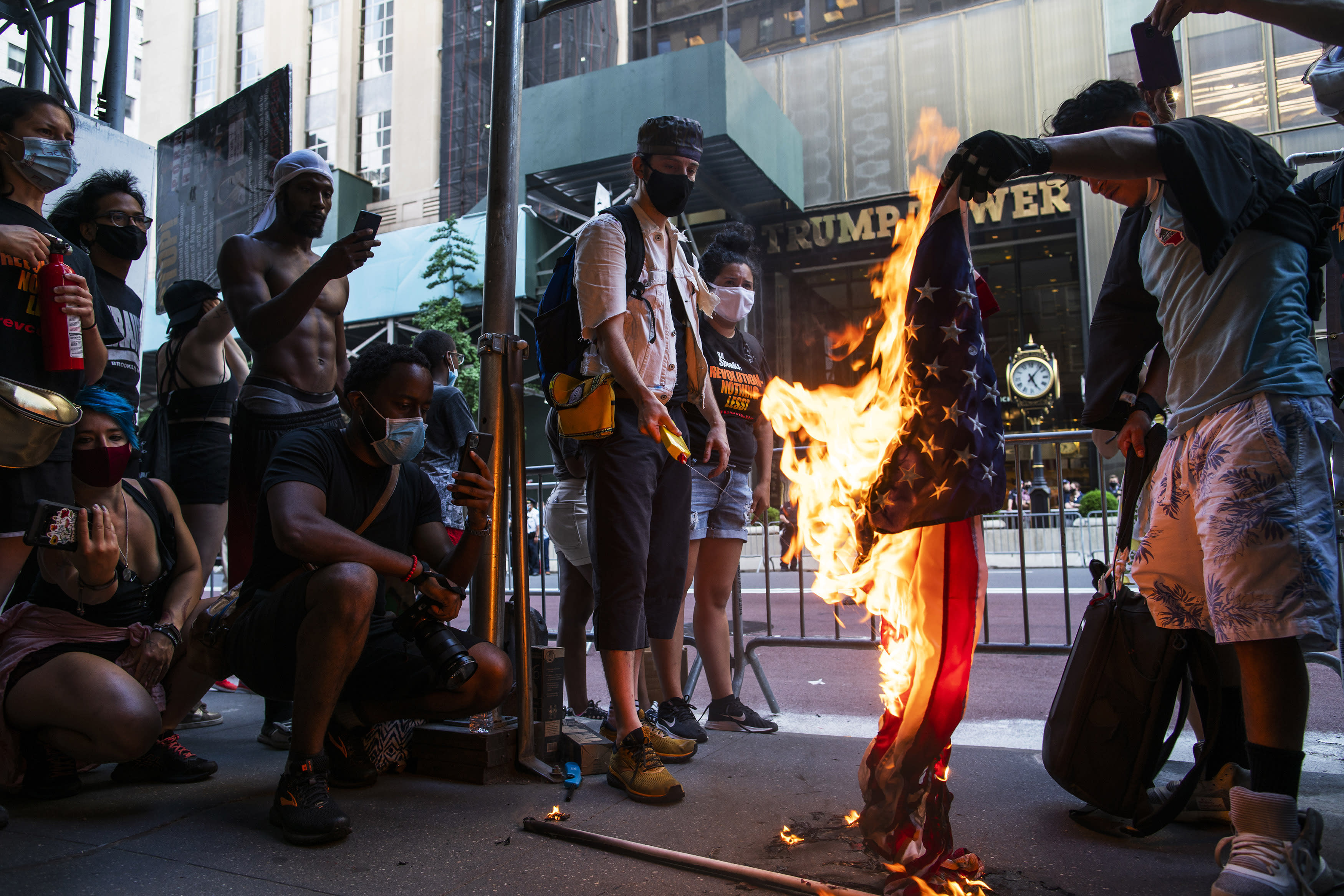 Protesters burn U.S. flags during a protest in front of Trump Tower, Saturday, July 4, 2020, in New York. (AP Photo/Eduardo Munoz Alvarez)