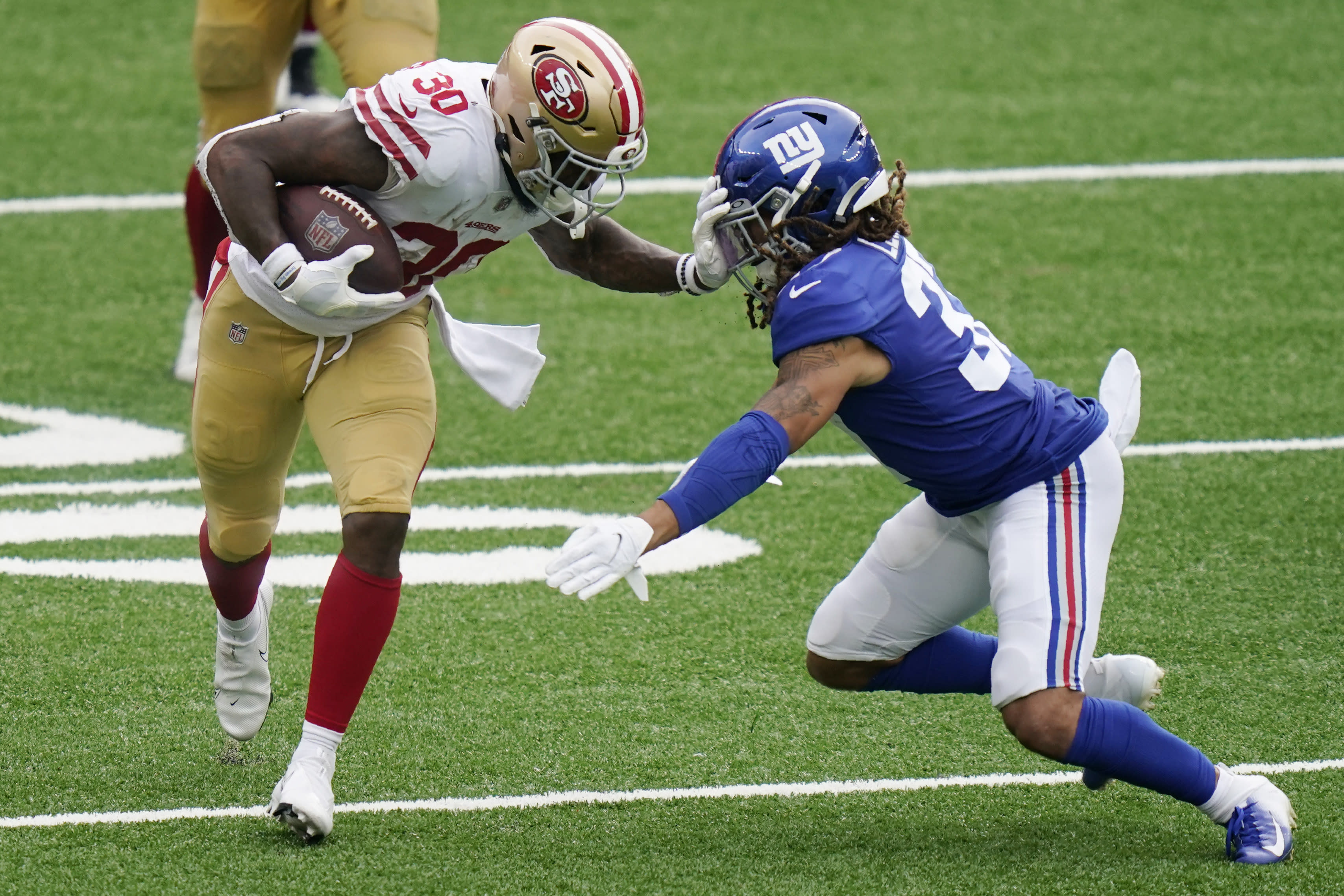 San Francisco 49ers' Jeff Wilson, left, fends off New York Giants' Ryan Lewis during the second half of an NFL football game, Sunday, Sept. 27, 2020, in East Rutherford, N.J. (AP Photo/Corey Sipkin)