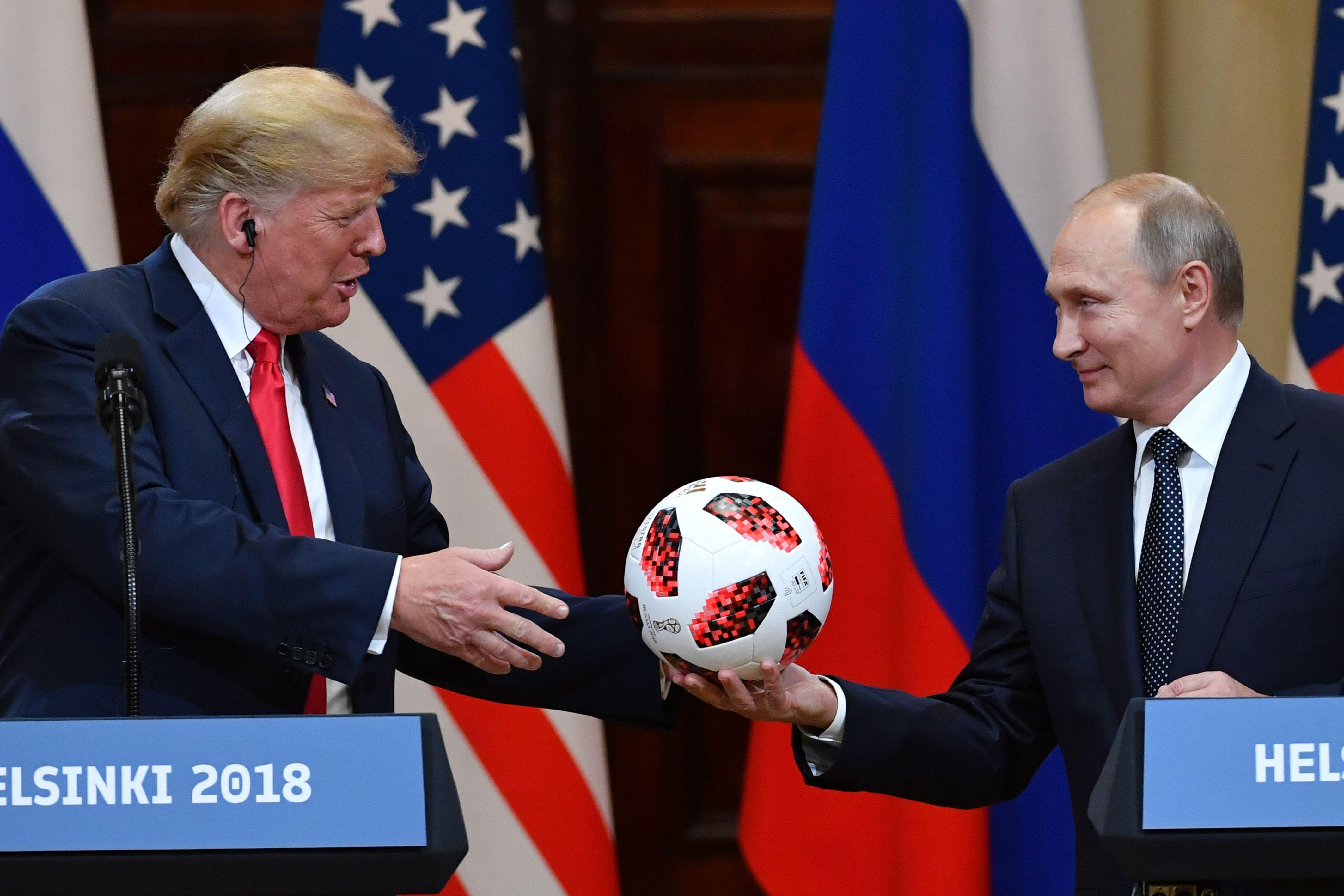<p>Russia's President Vladimir Putin offers a ball of the 2018 football World Cup to US President Donald Trump during a joint press conference after a meeting at the Presidential Palace in Helsinki, on July 16, 2018. (Photo: Yuri Kadobnov/AFP/Getty Images) </p>