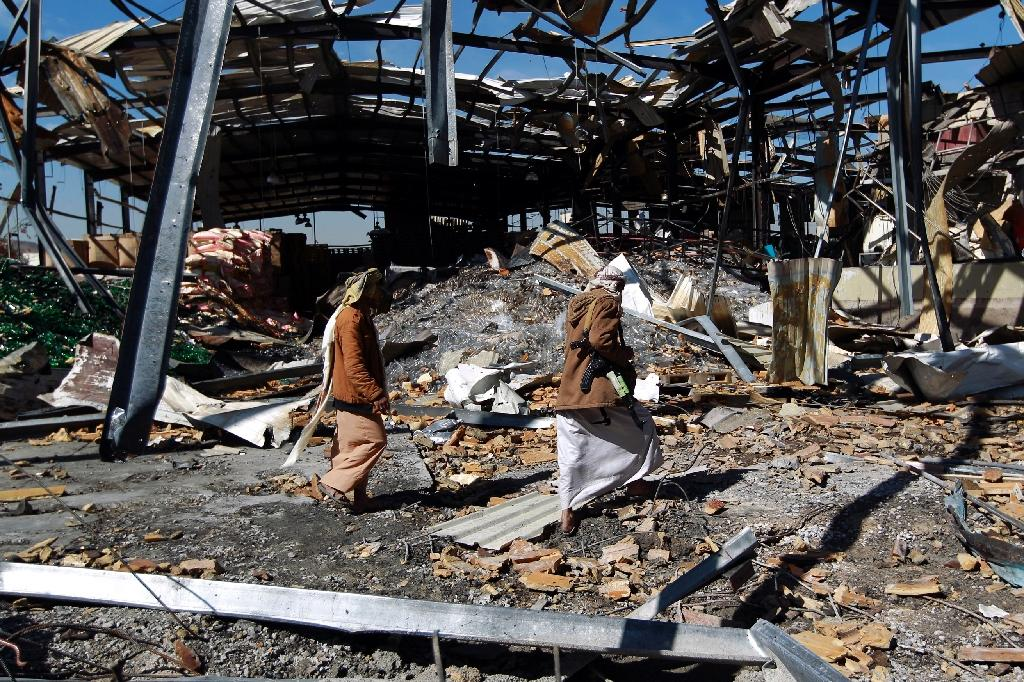 Yemeni workers inspect the damage at a factory after it was reportedly destroyed by Saudi-led airstrikes in the capital Sanaa