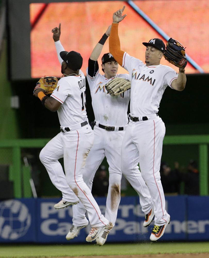 Marcell Ozuna (left) and Christian Yelich (center) celebrate with Giancarlo Stanton following his game-ending and home run-saving catch. (AP)