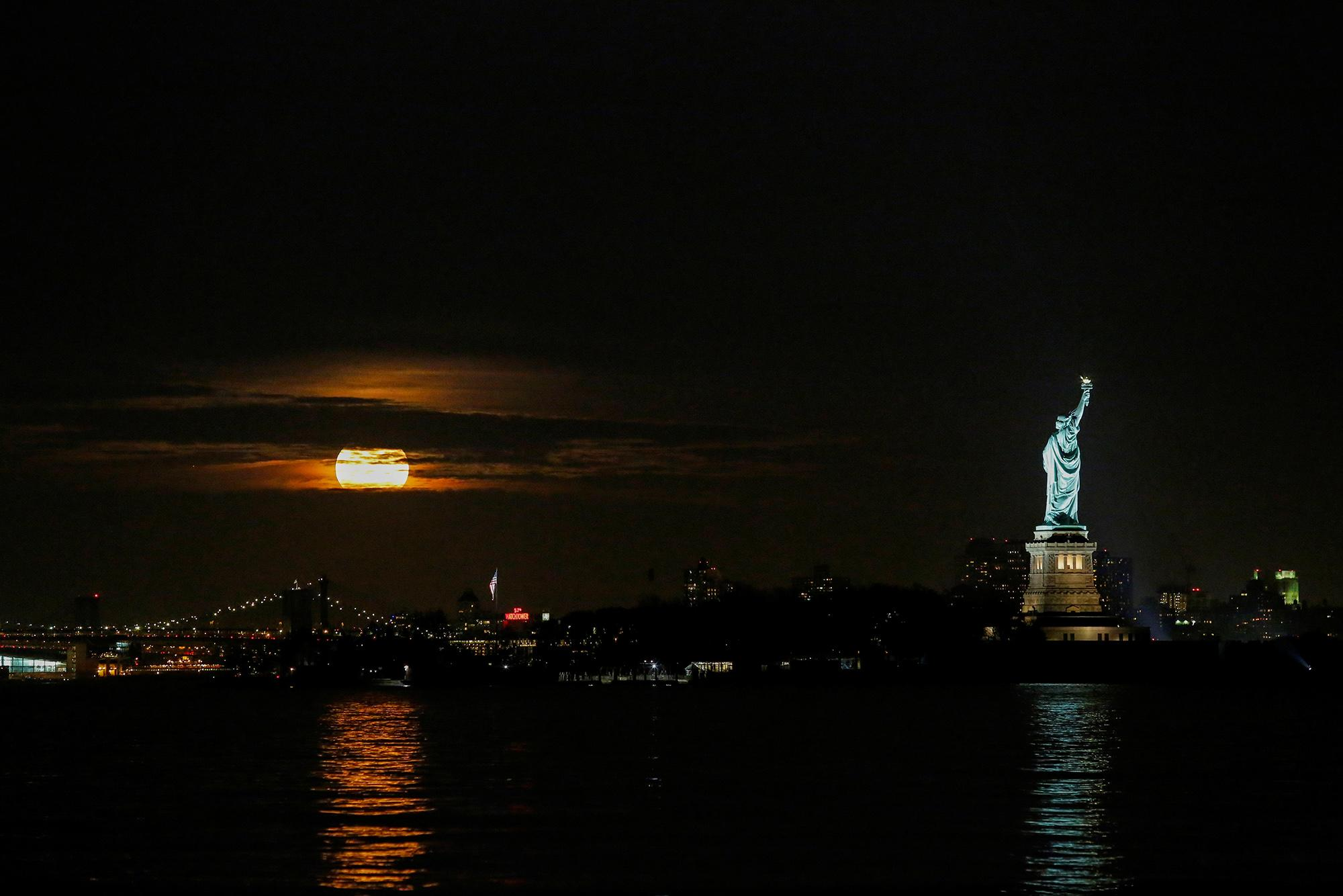 <p>The supermoon is seen through clouds over New York while it is seen from Bayonne in N.J., on Nov.14, 2016. (Eduardo Munoz/Reuters) </p>