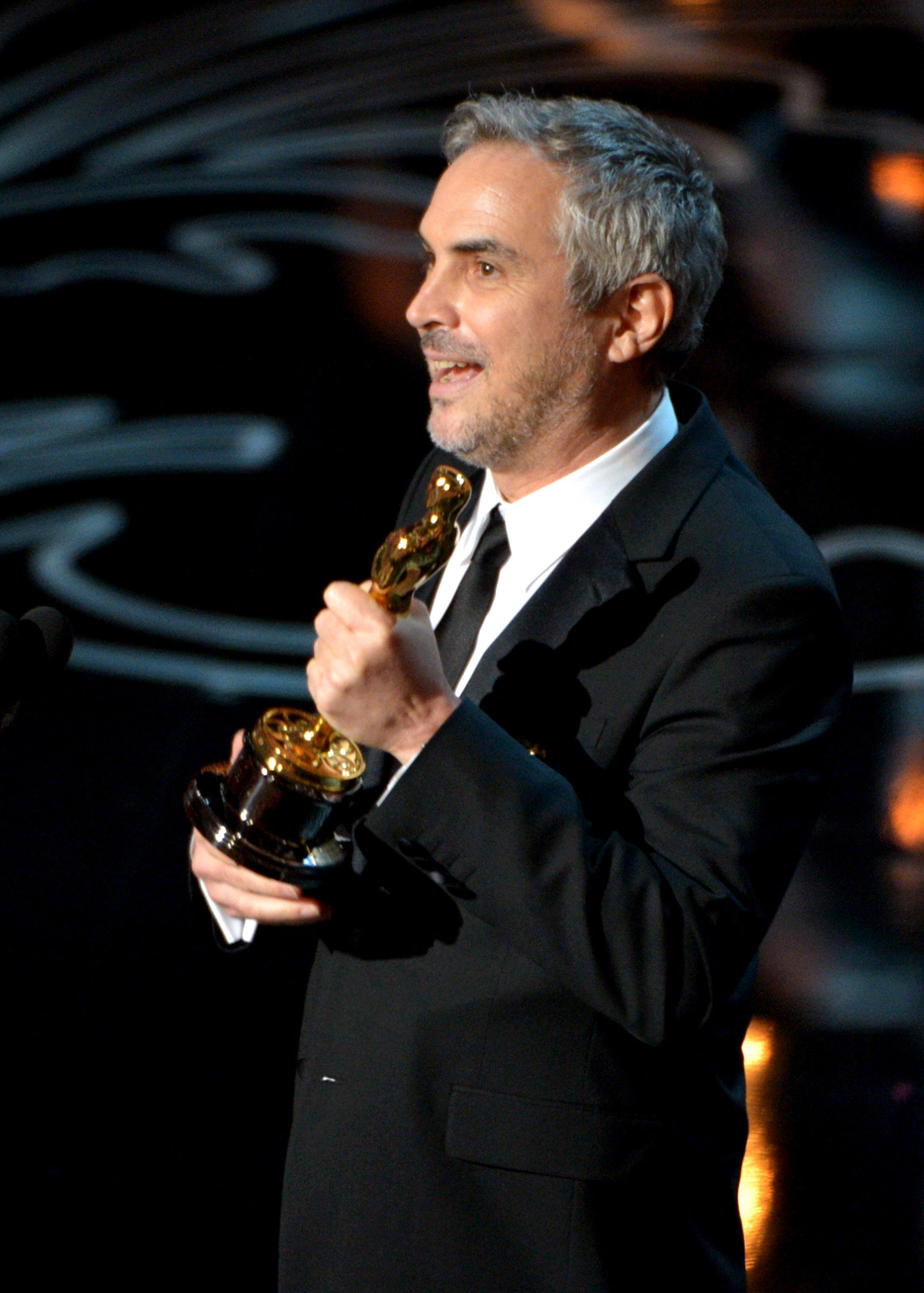 """Alfonso Cuaron accepts the award for best director for """"Gravity"""" during the Oscars at the Dolby Theatre on Sunday, March 2, 2014, in Los Angeles. (Photo by John Shearer/Invision/AP)"""
