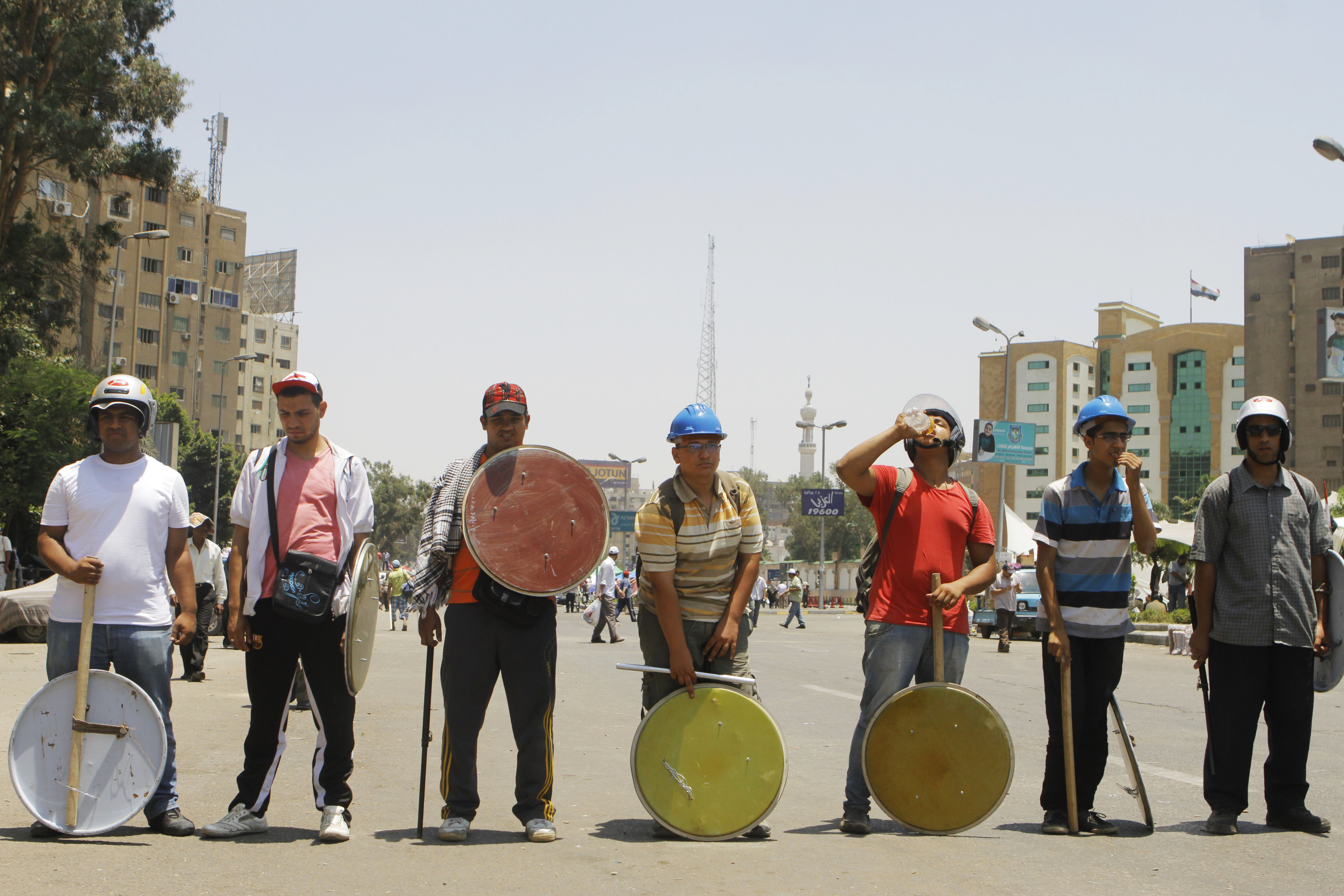 Supporters of Egypt's Islamist President Mohammed Morsi armed by sticks and shields to protect from stone attack guard their protesting site at a public square outside the Rabia el-Adawiya mosque near the presidential palace in Cairo, Saturday, June 29, 2013. Thousands of supporters and opponents of Egypt's embattled Islamist president held rival sit-ins in separate parts of Cairo Saturday on the eve of opposition-led mass protests aimed at forcing Mohammed Morsi from power. (AP Photo/Amr Nabil)