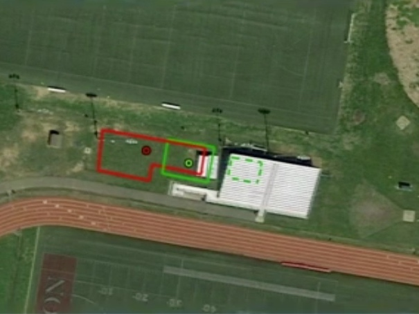 The original plan called for a 2,590 square foot, fenced-off compound located in the open space near the visitors bleachers. The revised plan (green) shifted the smaller compound partially under the bleachers.