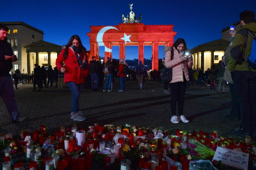 People leave flowers and candles at a makeshift memorial in front of Berlin's landmark Brandenburg Gate, illuminated in the colors of the Turkish flag, to pay tribute to the victims of the Reina night club attack (AFP Photo/Maurizio Gambarini)