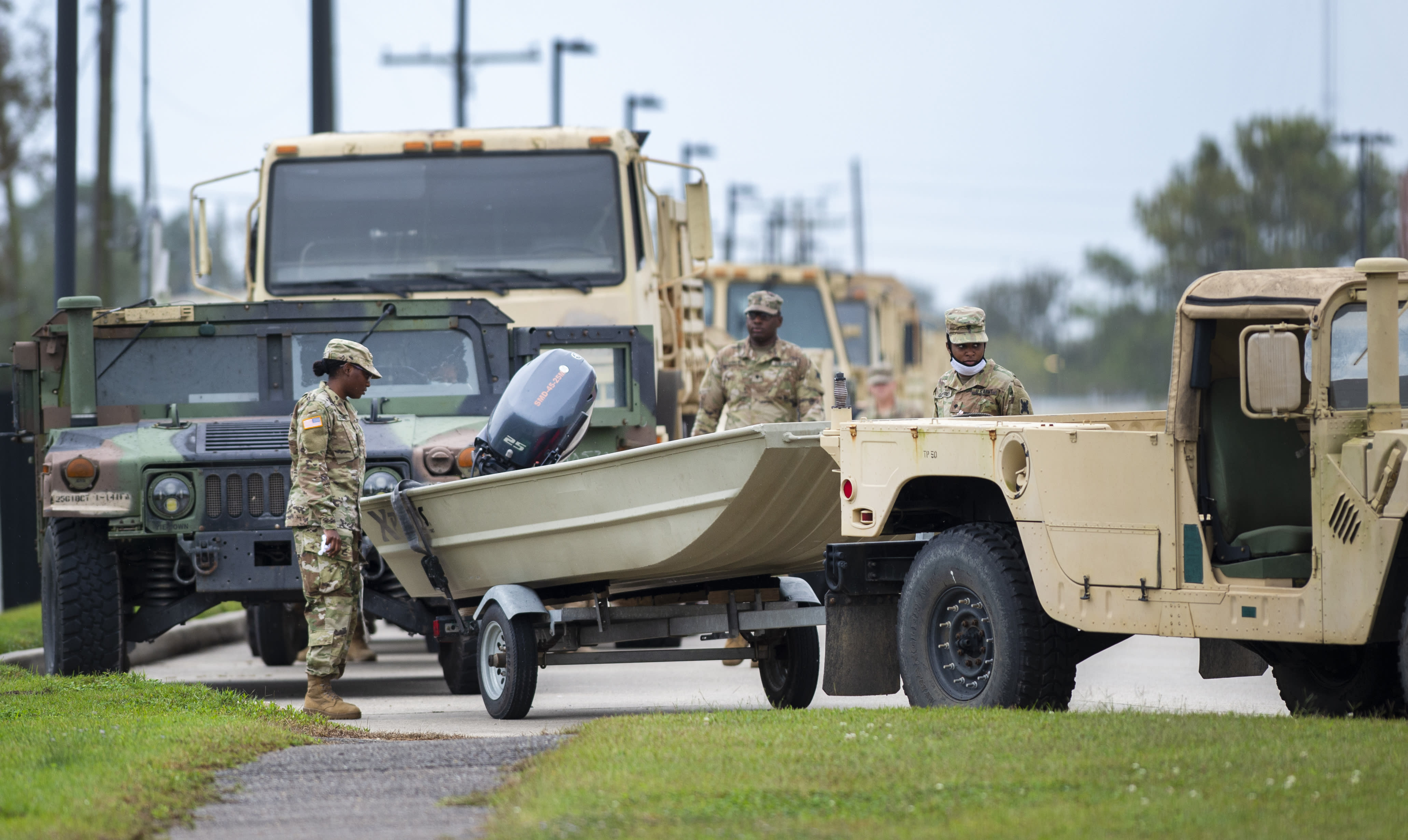 Dozens of boats trailered behind humvees are parked and ready to roll as Louisiana National Guardsmen gather in front of Jackson Barracks as the New Orleans area prepares for Hurricane Zeta on Wednesday, Oct. 28, 2020. (Chris Granger/The Times-Picayune/The New Orleans Advocate via AP)