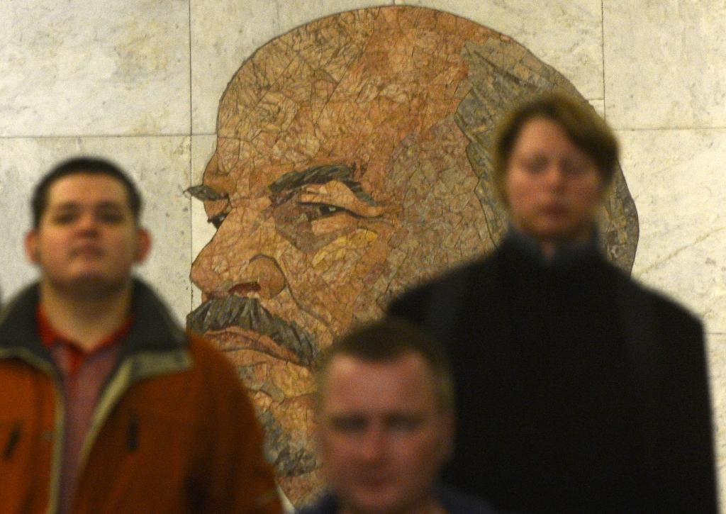 Subway passengers walk past a huge portrait of the Soviet Union founder Vladimir Lenin in a vestibule of the Biblioteka Imeni Lenina metro station in Moscow on November 14, 2012 (AFP Photo/Kirill Kudryavtsev)