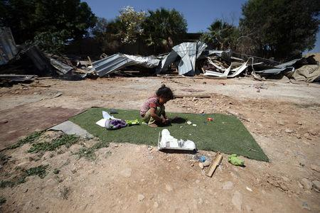 A Palestinian girl plays outside her family structure after it was demolished by Israeli forces near the West Bank city of Jericho April 7, 2016. REUTERS/Mohamad Torokman
