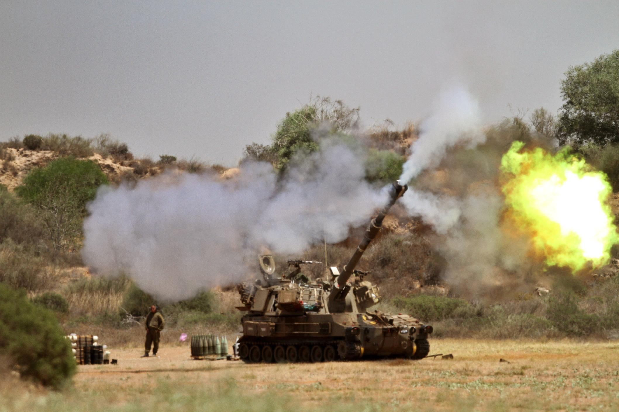 Israeli soldiers fire towards the Gaza Strip from their position near Israel's border with the coastal Palestinian enclave on July 27, 2014