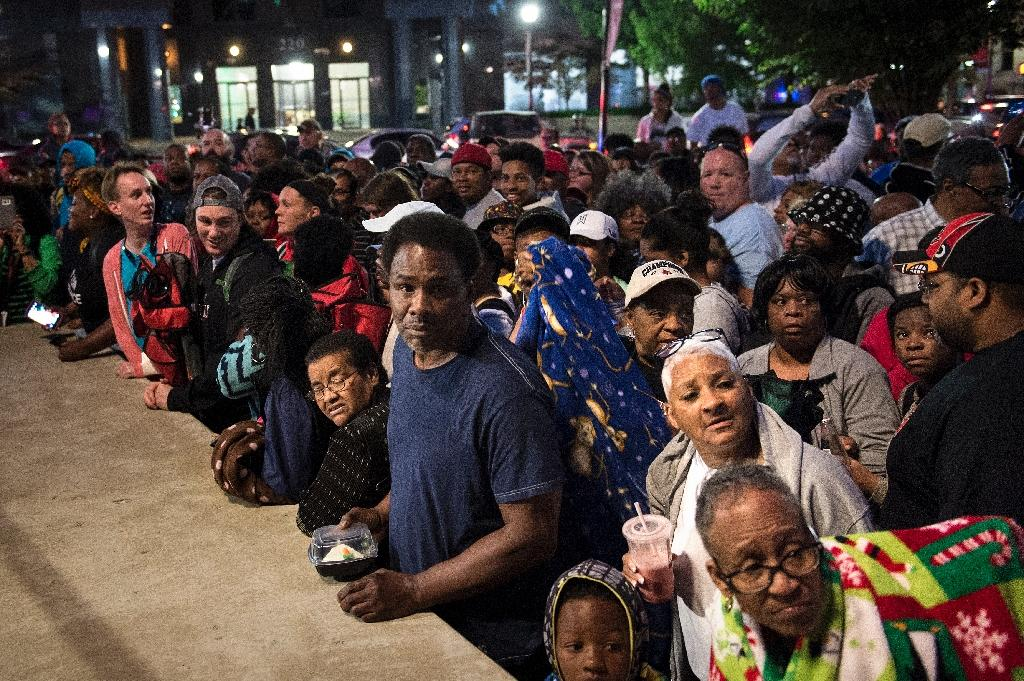People line up for tickets to a memorial service outside the KFC Yum! Center. (AFP Photo/Brendan Smialowski)
