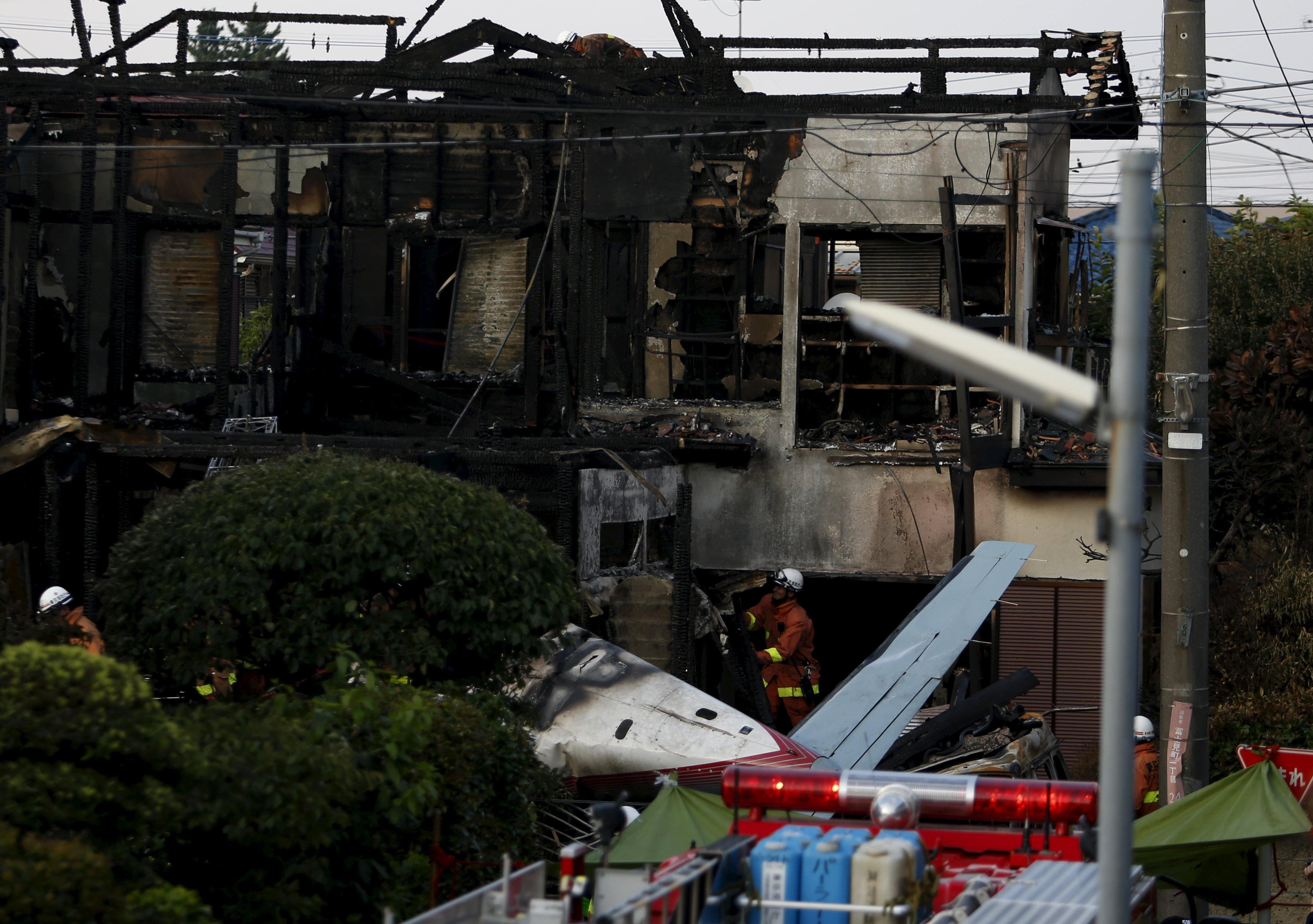 Firefighters remove wreckage and debris at the site where a light plane went down in a residential area and burst into flames, in Chofu, outskirt of Tokyo, July 26, 2015. Three people were killed when a small airplane crashed into a residential area of the Japanese capital, Tokyo, on Sunday, public broadcaster NHK reported, setting fire to houses and cars. REUTERS/Yuya Shino