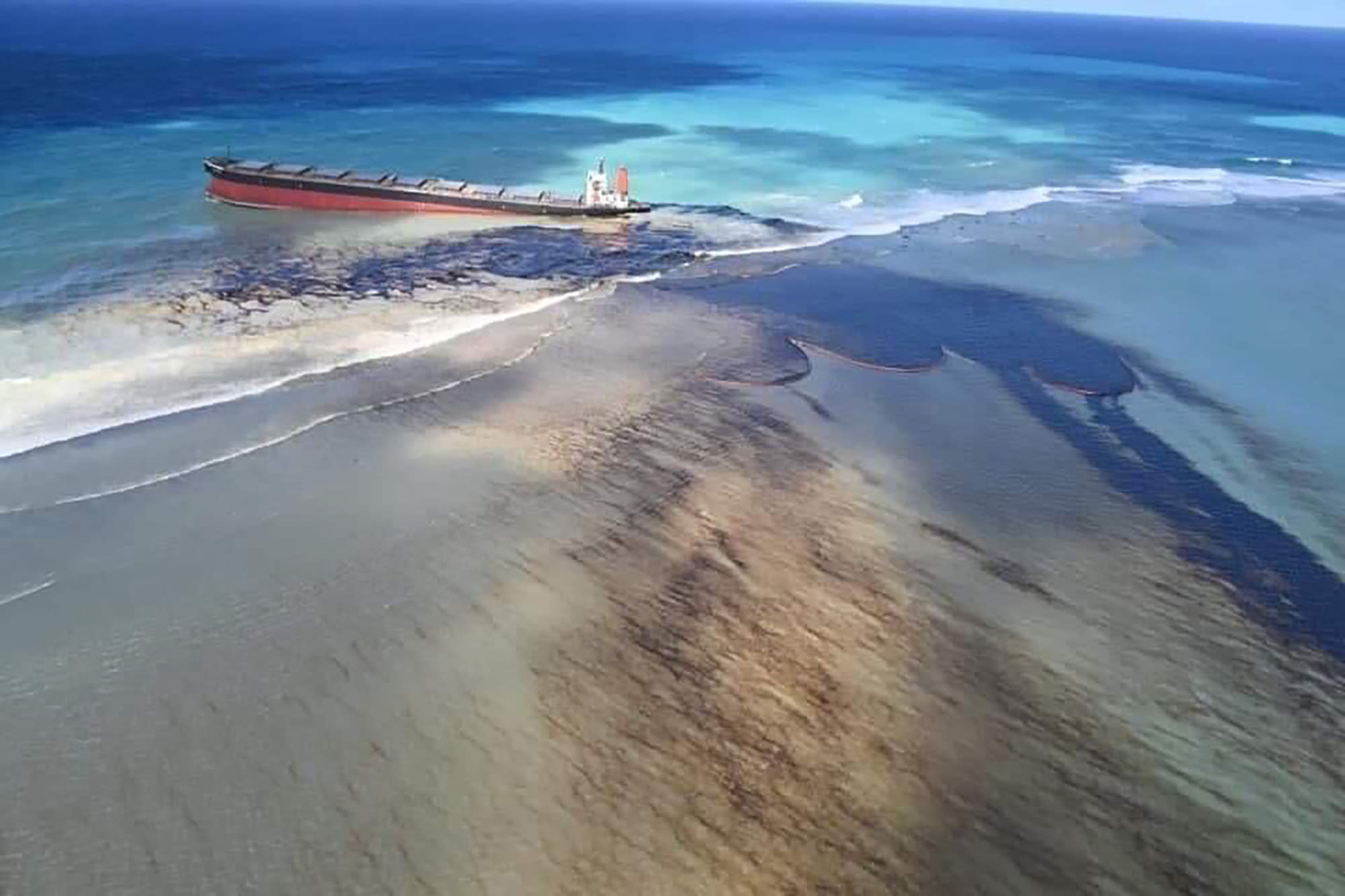 "This photo taken and provided by Georges de La Tremoille of Mu Press shows oil leaking from the MV Wakashio, a bulk carrier ship that recently ran aground off the southeast coast of Mauritius, Friday, Aug. 7, 2020. The Indian Ocean island of Mauritius declared a ""state of environmental emergency"" late Friday after a Japanese-owned ship that ran aground offshore days ago began spilling tons of fuel. (Georges de La Tremoille/MU press via AP)"