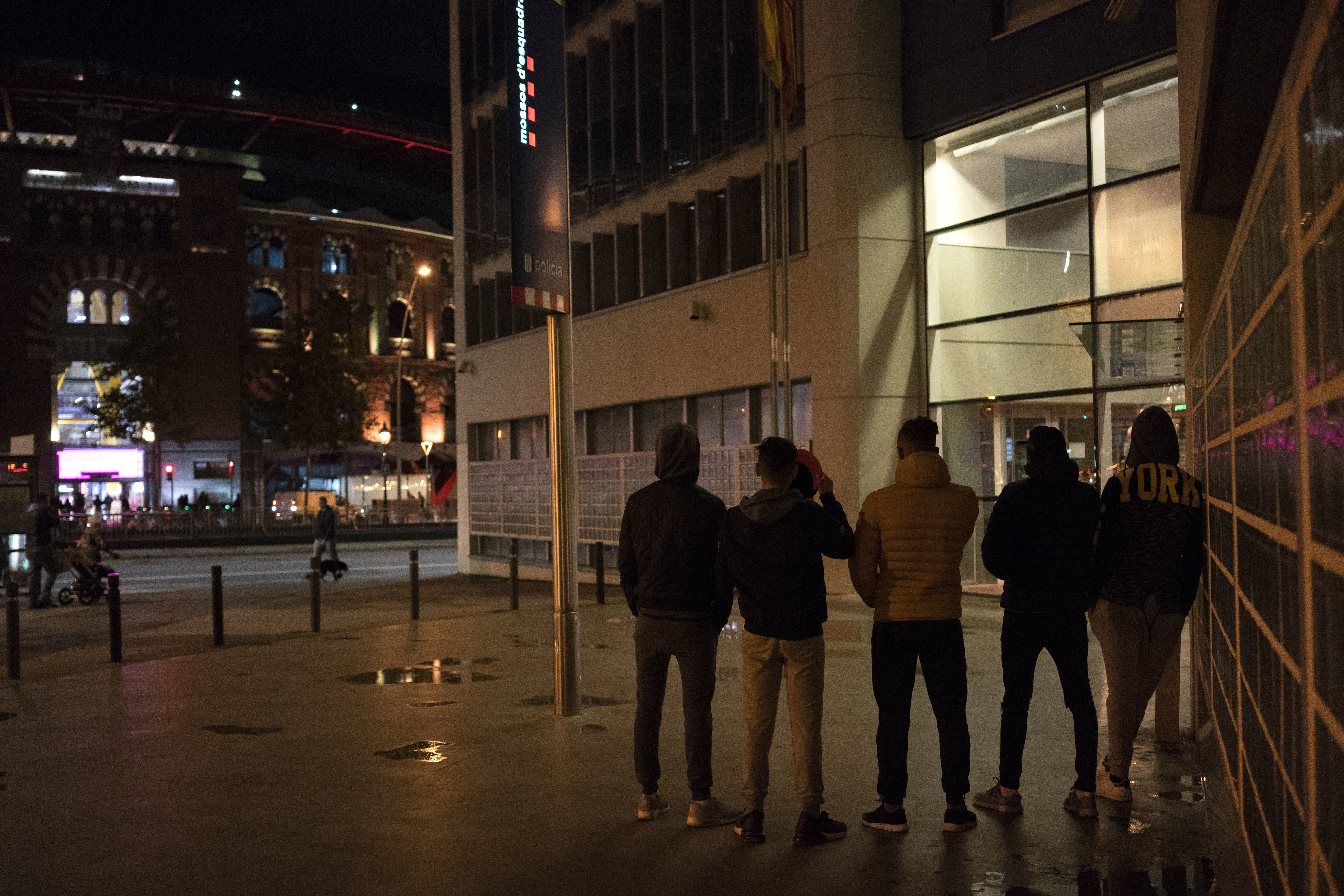 In this Nov. 9, 2018 photo, unaccompanied minors from Morocco seeking shelter, stand outside a police station in Barcelona, Spain. Slouched on a bench at a Barcelona police station, five teenagers waited patiently on a recent Friday evening to find out where they would sleep that night: a shelter for young migrants or on that bench. (AP Photo/Renata Brito)