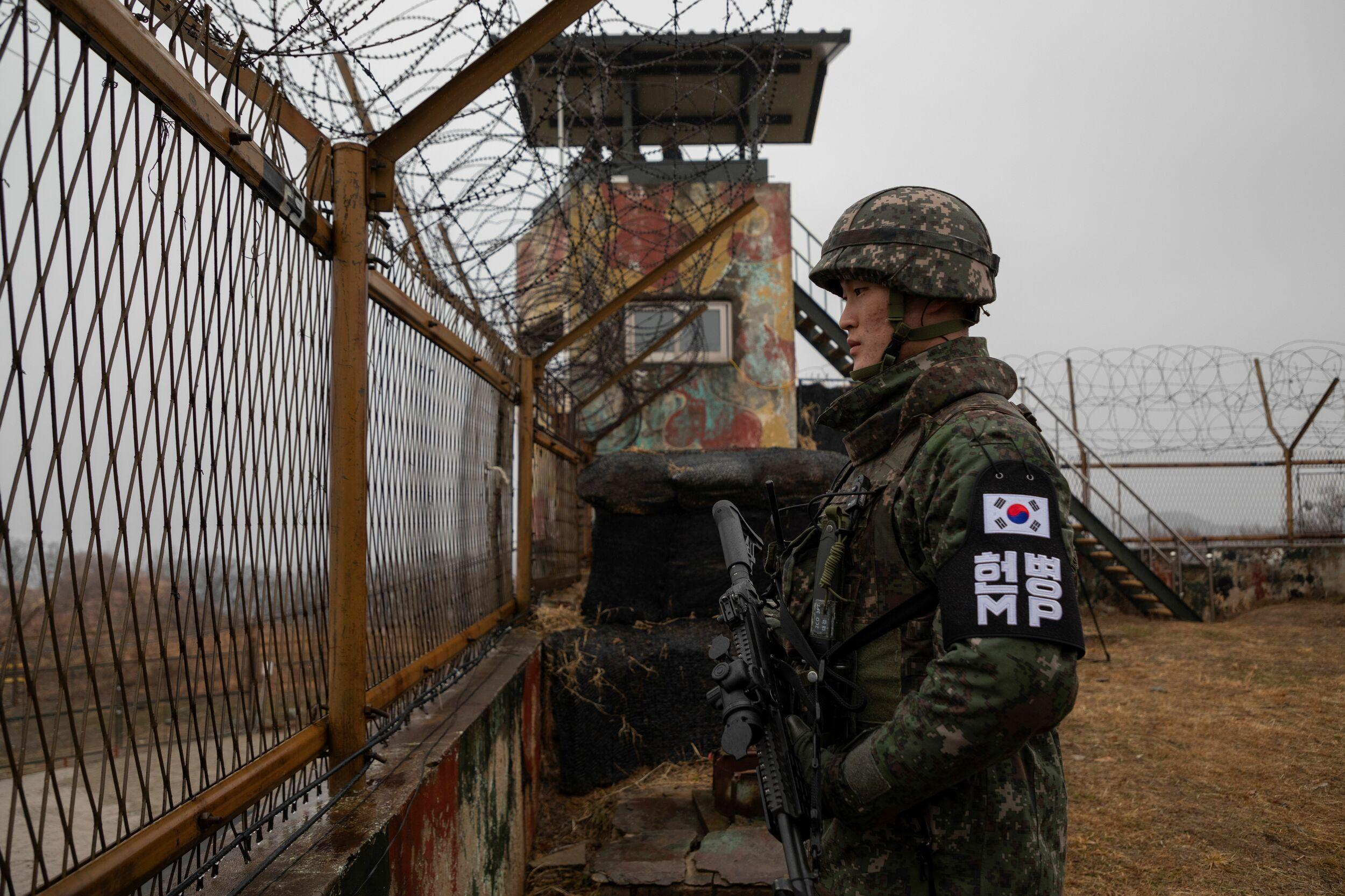 In a photo taken on December 3, 2018 a South Korean soldier stands before a security fence at a guard post inside the Demilitarized Zone (DMZ) near the Military Demarcation Line (MDL) separating North and South Korea, in South Korea's Cheorwon county. (Photo by Yelim LEE / AFP)        (Photo credit should read YELIM LEE/AFP/Getty Images)