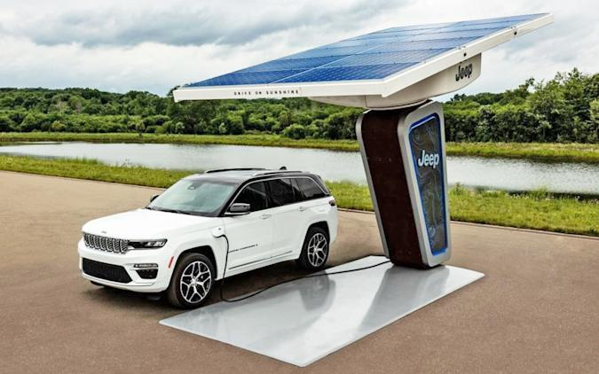 A fully electric 4xe Jeep parked at a charging station by the water.