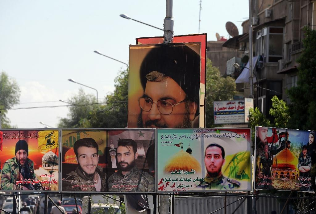 A portrait of Hassan Nasrallah (top), the head of Lebanon's militant Shiite Muslim movement Hezbollah, and portraits of pro-government forces members killed in combat displayed on a street in the Syrian capital, Damascus (AFP Photo/Joseph Eid)