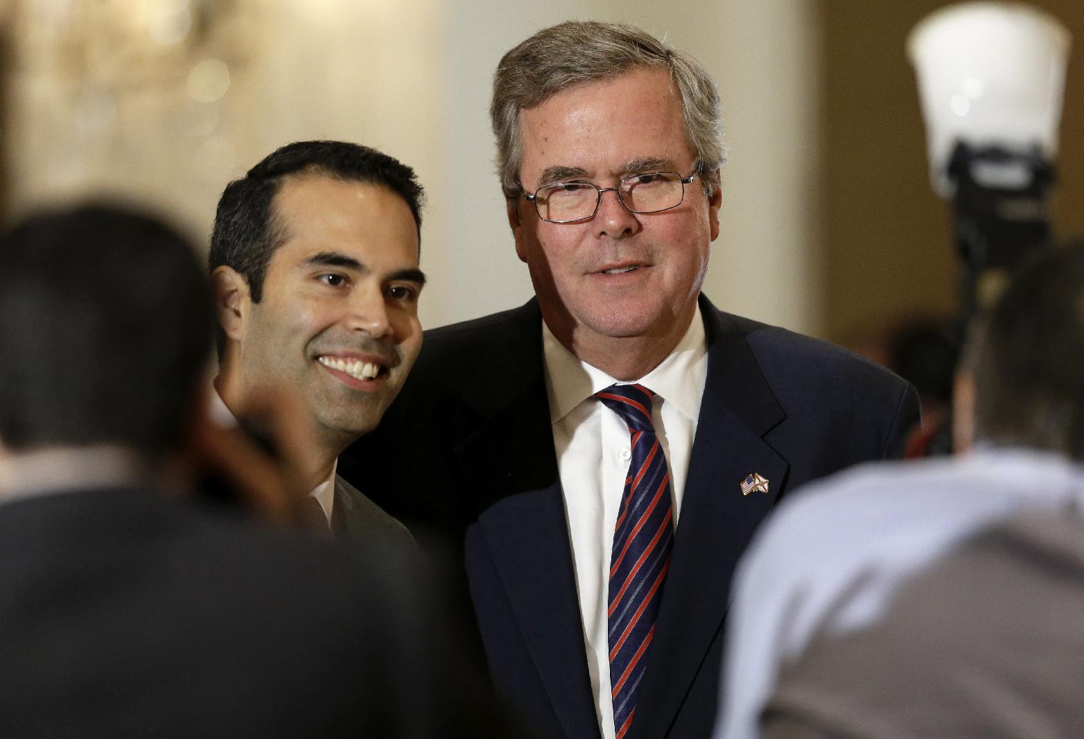 George P. Bush, left, poses for photos with his dad, former governor Jeb Bush, right, before a Dallas Council of World Affairs luncheon where Jeb was the featured speaker Wednesday, April 24, 2013, in Dallas. Jeb Bush and Hillary Rodham Clinton are hitting the speakers' circuit on the eve of the opening of George W. Bush's new presidential library, stoking speculation about their own political futures. (AP Photo/Tony Gutierrez)