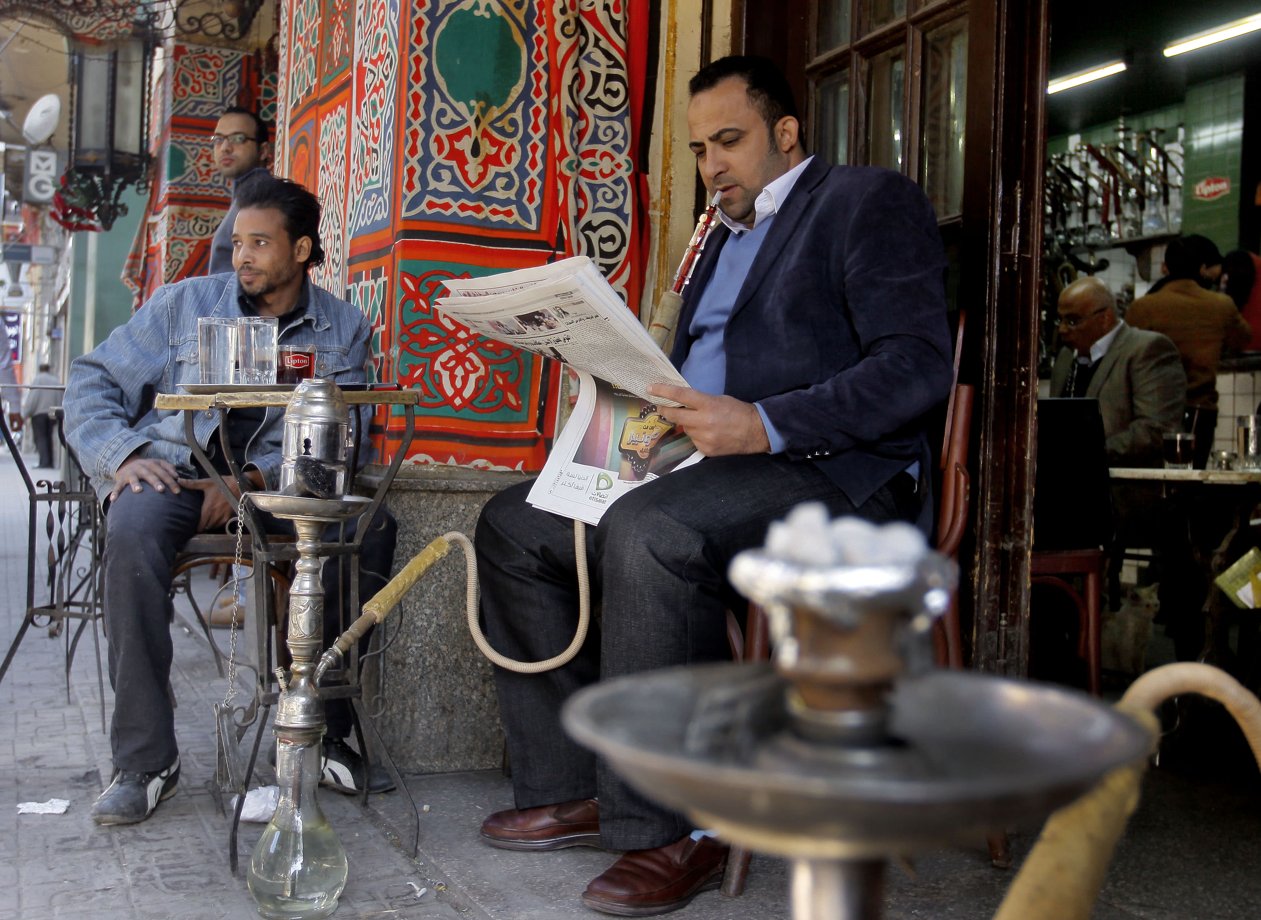 """An Egyptian man reads a newspaper at a coffee shop in Cairo, Egypt, Sunday, Dec. 23, 2012. Egypt's opposition called Sunday for an investigation into allegations of vote fraud in the referendum on a deeply divisive Islamist-backed constitution after the Muslim Brotherhood, the main group backing the charter, claimed it passed with a 64 percent """"yes"""" vote. Official results have not been released yet and are expected on Monday. (AP Photo/Amr Nabil)"""