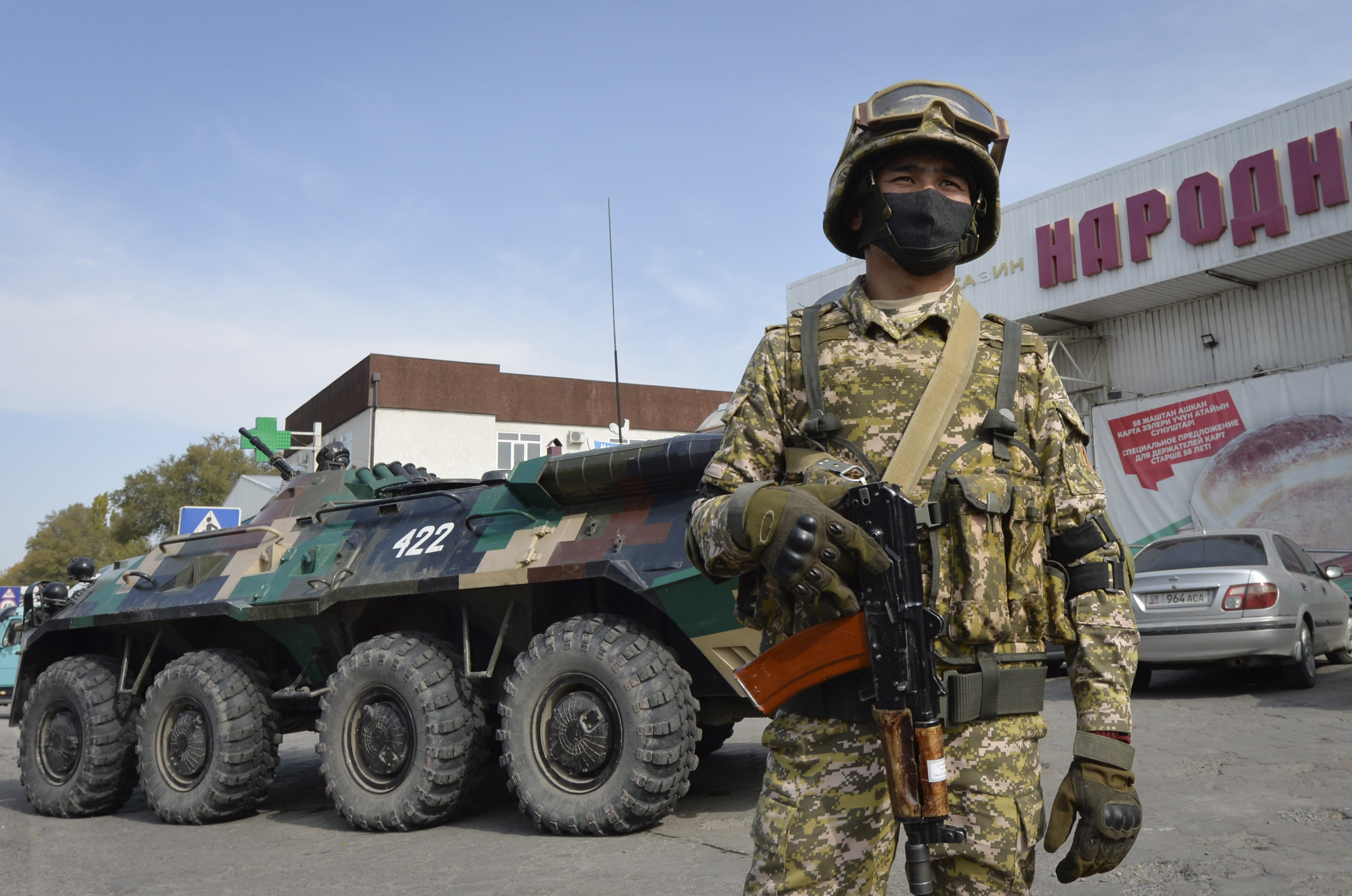 Soldiers of Kyrgyz army stand at checkpoint on city street in Bishkek, Kyrgyzstan, Saturday, Oct. 10, 2020. President Sooronbai Jeenbekov decreed the state of emergency in the capital and ordered the military to deploy troops to Bishkek to enforce the measure. (AP Photo/Vladimir Voronin)