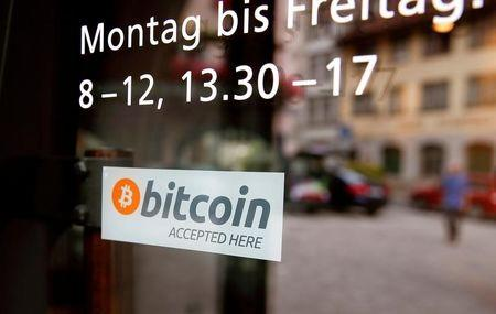 """A sticker that reads """"Bitcoin accepted here"""" is displayed at the entrance of the Stadthaus town hall in Zug"""