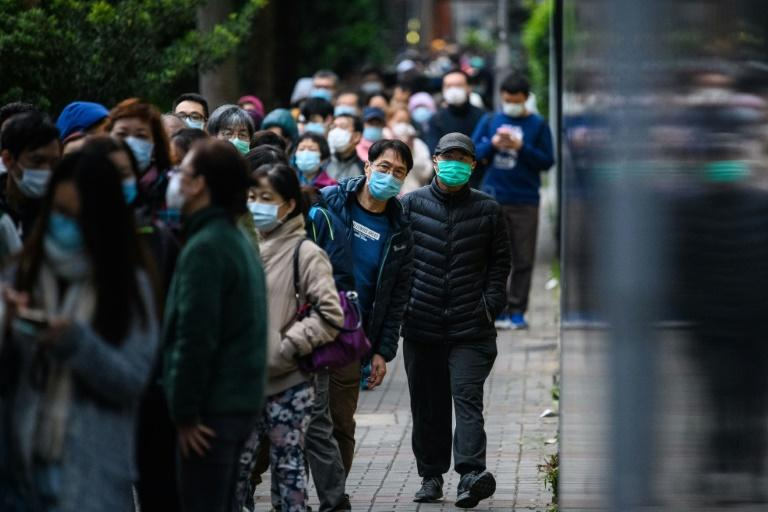 People queue for hours to purchase face masks from a makeshift stall in Hong Kong (AFP Photo/Anthony WALLACE)