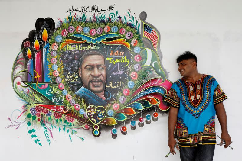 FILE PHOTO: Pakistani truck-art painter Haider Ali, 40, poses for a photograph next to a mural, depicting George Floyd, who died in Minneapolis police custody in U.S., in Karachi