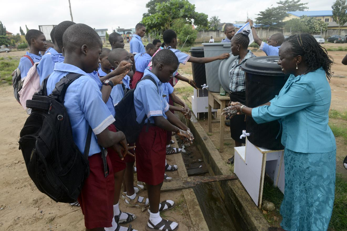 A teacher demonstrates washing procedures to pupils prevent the spread of the Ebola virus at a school in Lagos on October 8, 2014 (AFP Photo/Pius Utomi Ekpei)
