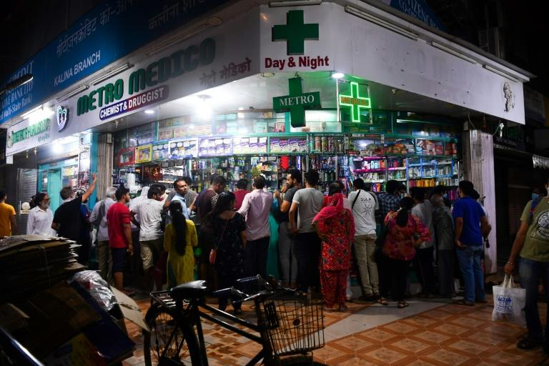 People gather at a pharmacy in Mumbai following the Indian prime minister's announcement of a government-imposed nationwide lockdown (AFP Photo/Indranil MUKHERJEE)