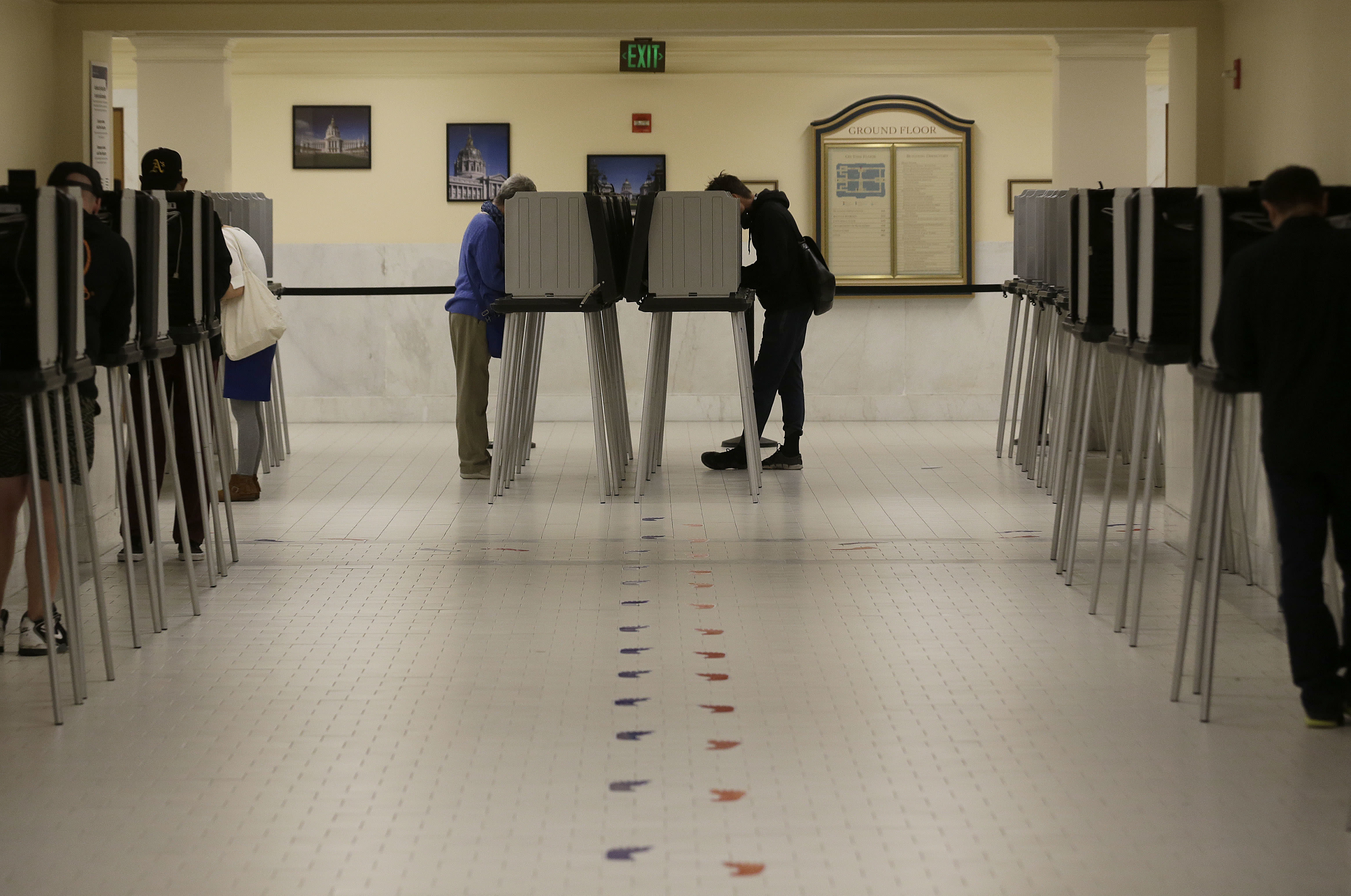 File - In this June 7, 2016 file photo, voters cast ballots in voting booths at City Hall in San Francisco. San Francisco will become the first city in California and one of only a handful nationwide to allow noncitizens to vote in a local election in November. They're only allowed to vote in the school board race. (AP Photo/Jeff Chiu, File)