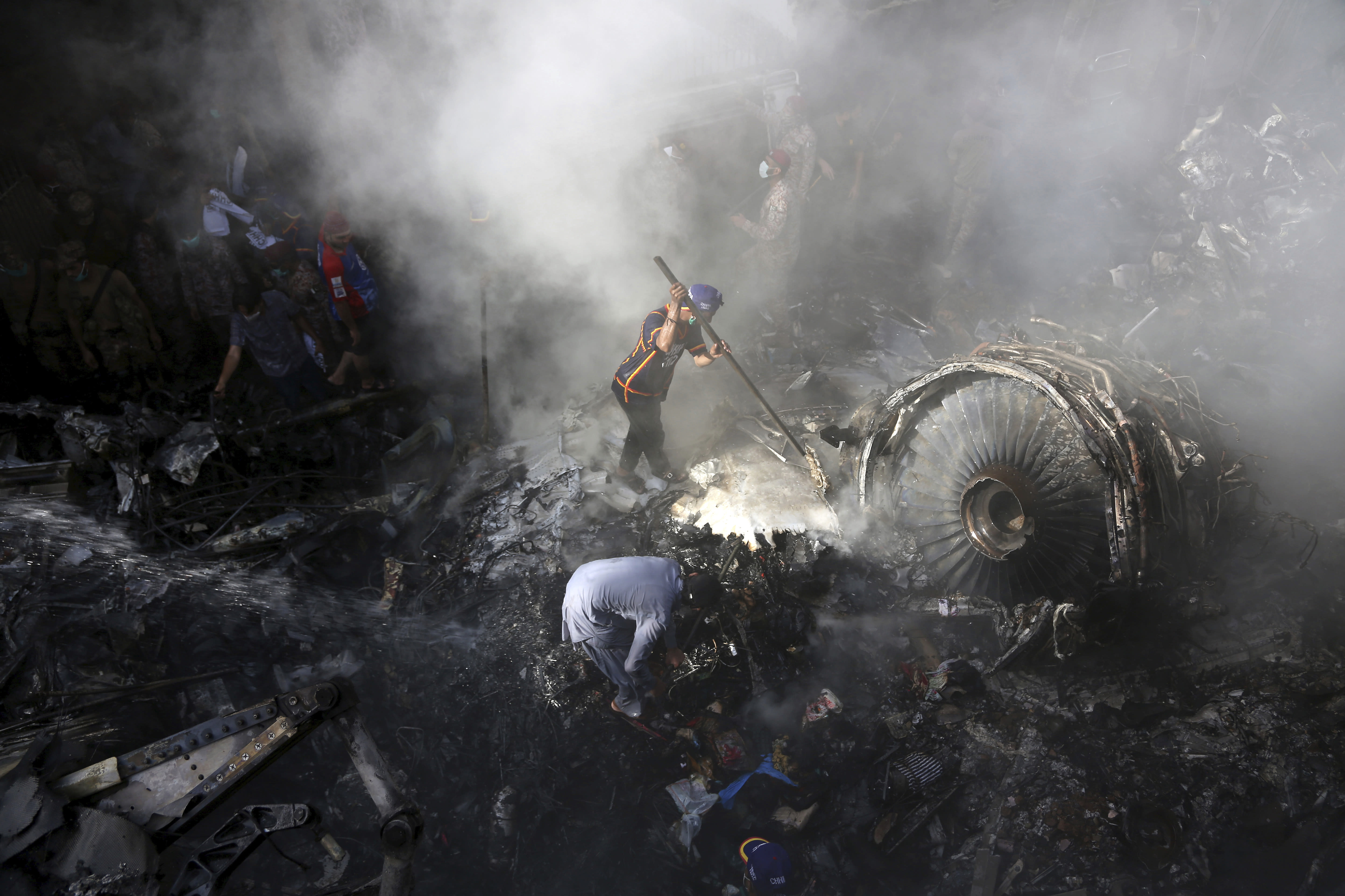 FILE - In this May 22, 2020 file photo, volunteers look for survivors of a Pakistan International Airlines plane that crashed in a residential area of Karachi, Pakistan. The spokesman of Pakistan's national carrier said Wednesday, July 8, 2020, that the airline is firing 28 pilots found to have tainted licenses, the latest chapter in a scandal that emerged in the wake of the Airbus A320 crash in Karachi in May. An inquiry into the crash, which killed 97 people on board, resulted in the stunning revelation that 260 of 860 pilots in Pakistan had cheated on their pilots exams, but were still given licences by the Civil Aviation Authority. (AP Photo/Fareed Khan, File)