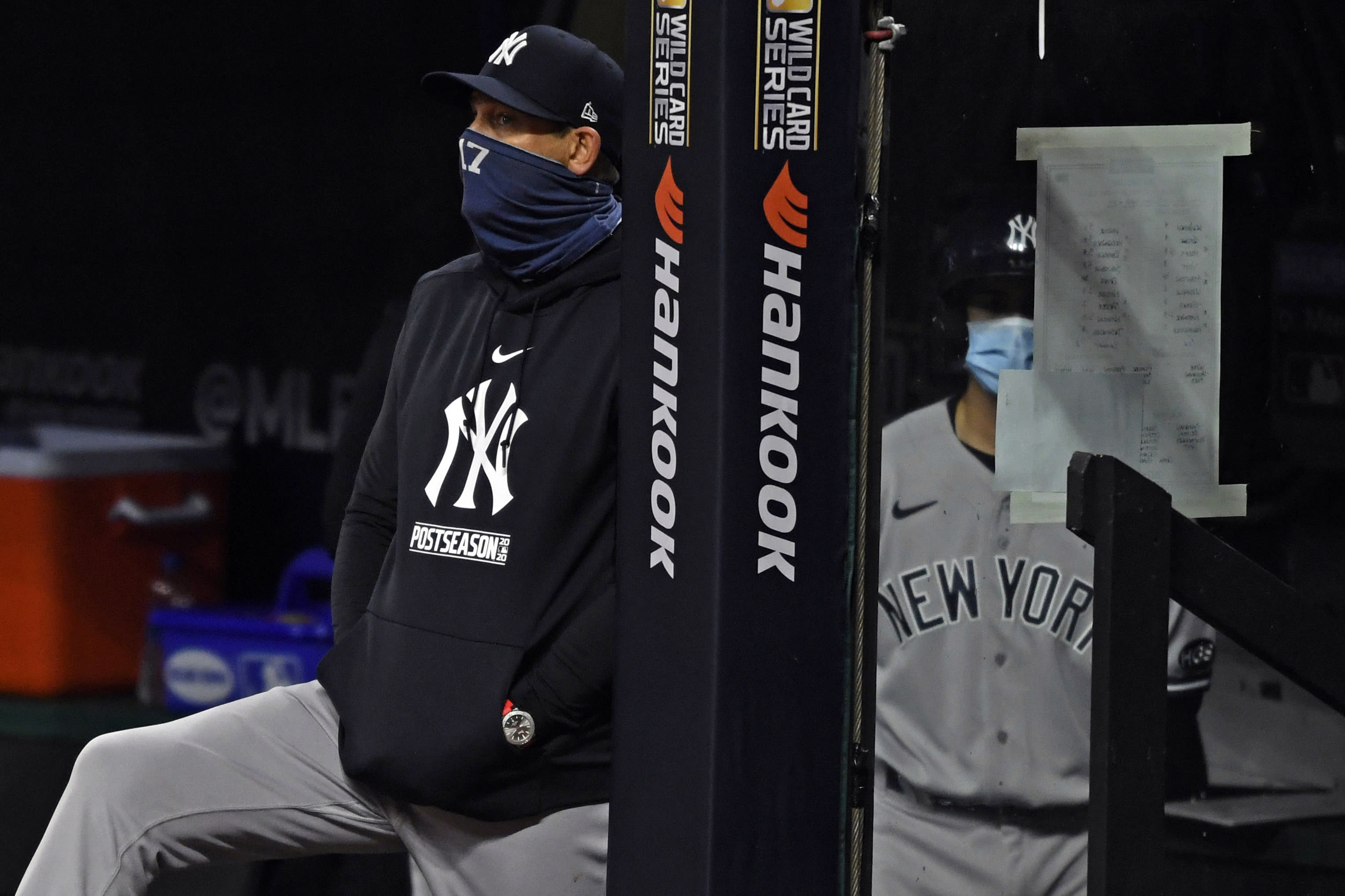 FILE - In this Tuesday, Sept. 29, 2020, file photo, New York Yankees manager Aaron Boone watches from the dugout in the sixth inning of Game 1 of an American League wild-card baseball series against the Cleveland Indians in Cleveland. (AP Photo/David Dermer, File)