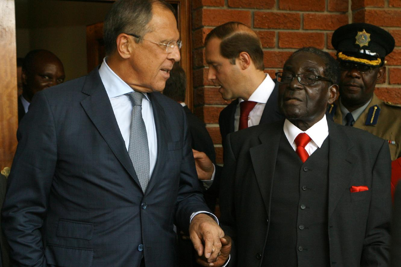 Russian Foreign Minister Sergei Lavrov (L) and Zimbabwean President Robert Mugabe shake hands after a meeting in Zvimba, Zimbabwe, on September 16, 2014